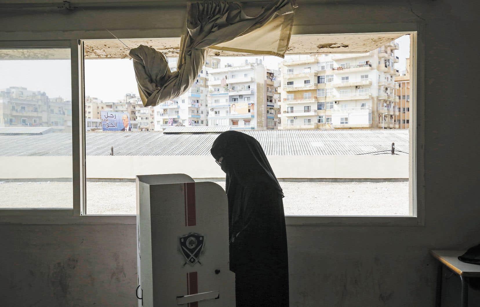 Une femme sunnite portant le voile intégral exerçait son droit de vote derrière un isoloir, dans un bureau de scrutin de Tripoli, au Liban, dimanche.