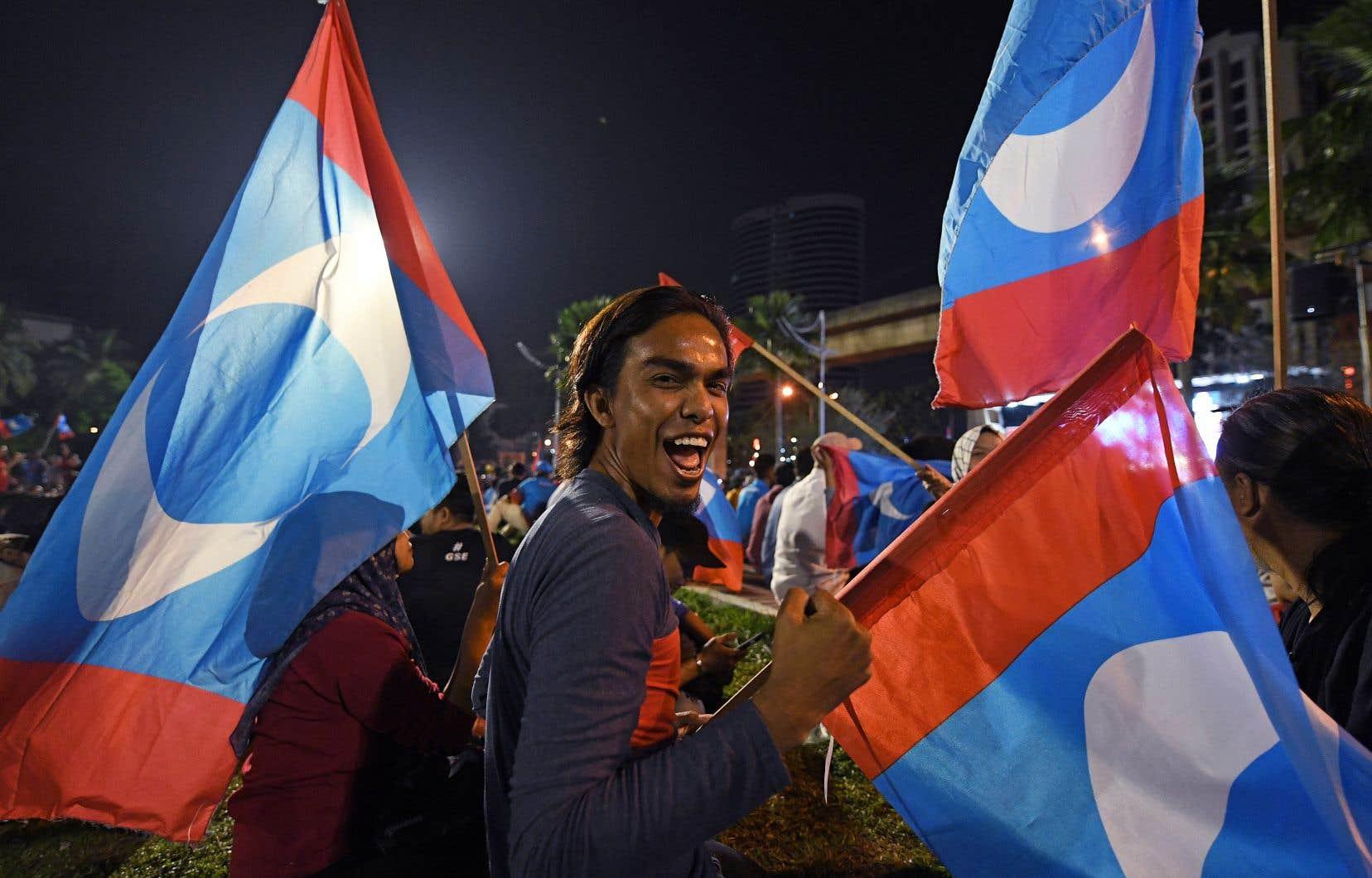 Un partisan de l'ancien premier ministre et candidat de l'opposition Mahathir Mohamad célèbre la victoire de son candidat à Kuala Lampur.