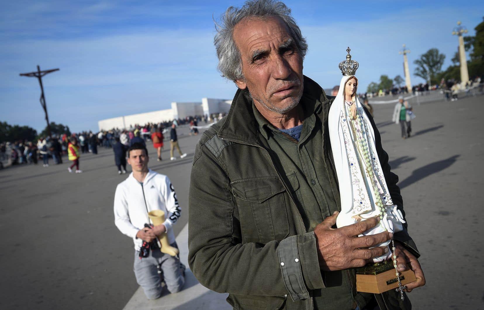 Un pèlerin transportait une statuette à l'effigie de la Vierge Marie, au sanctuaire de Notre-Dame-de-Fatima, dimanche.