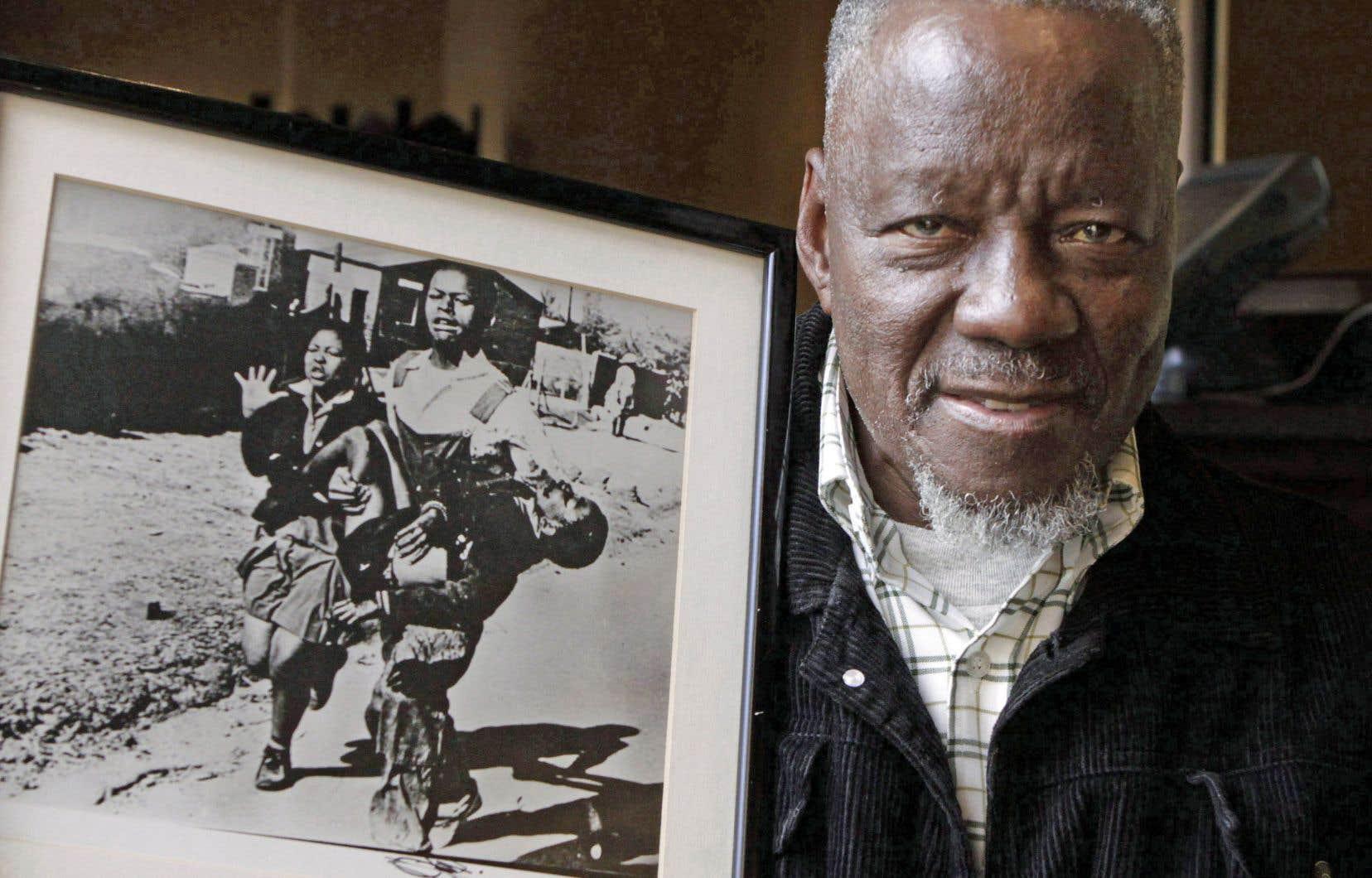 Le photographe pose ici en 2011 avec un encadrement de sa photo iconique du petit Hector Pieterson, mort sous les balles policières à Pretoria, en 1976.