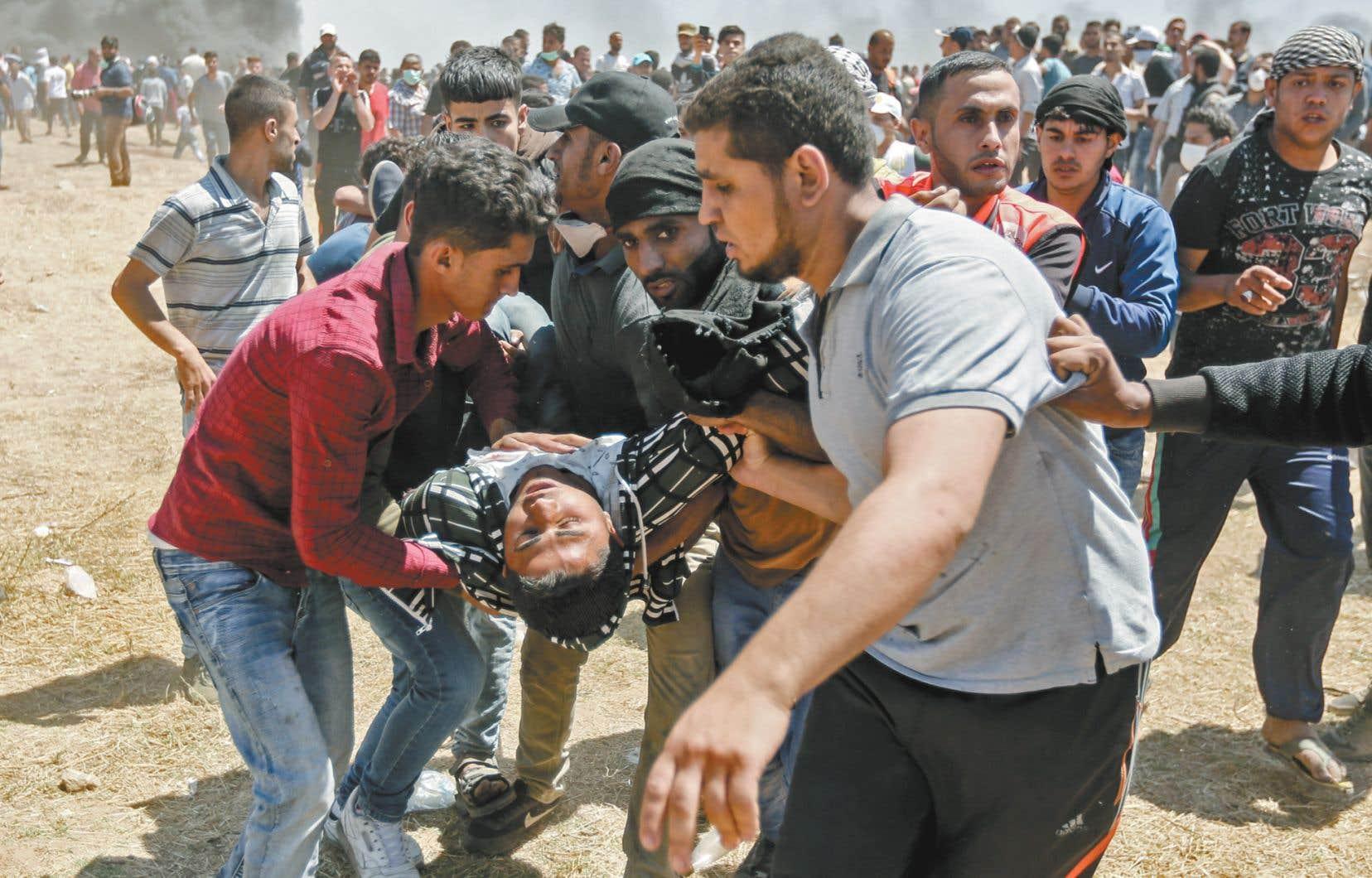 Des manifestants palestiniens évacuent un homme blessé lors des affrontements lundi avec les forces israéliennes à la frontière de la bande de Gaza.