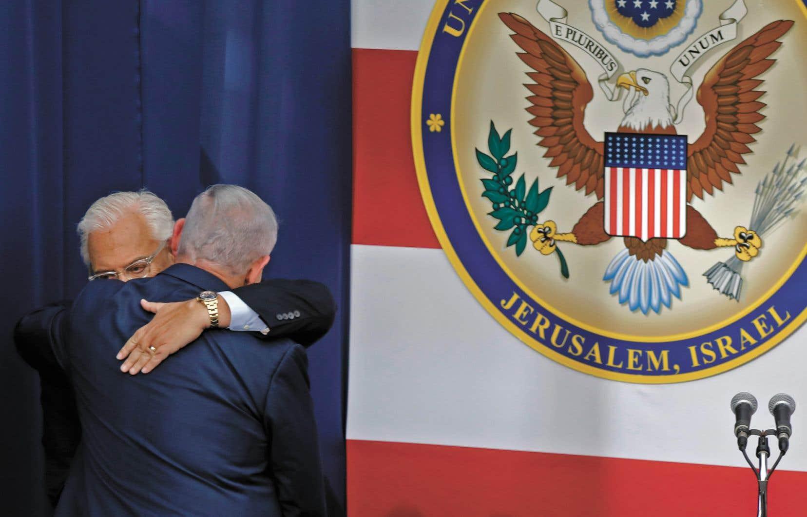 L'ambassadeur américain en Israël, David Friedman, et le premier ministre israélien, Benjamin Netanyahou, se sont donné l'accolade sur scène, dimanche, à Jérusalem.