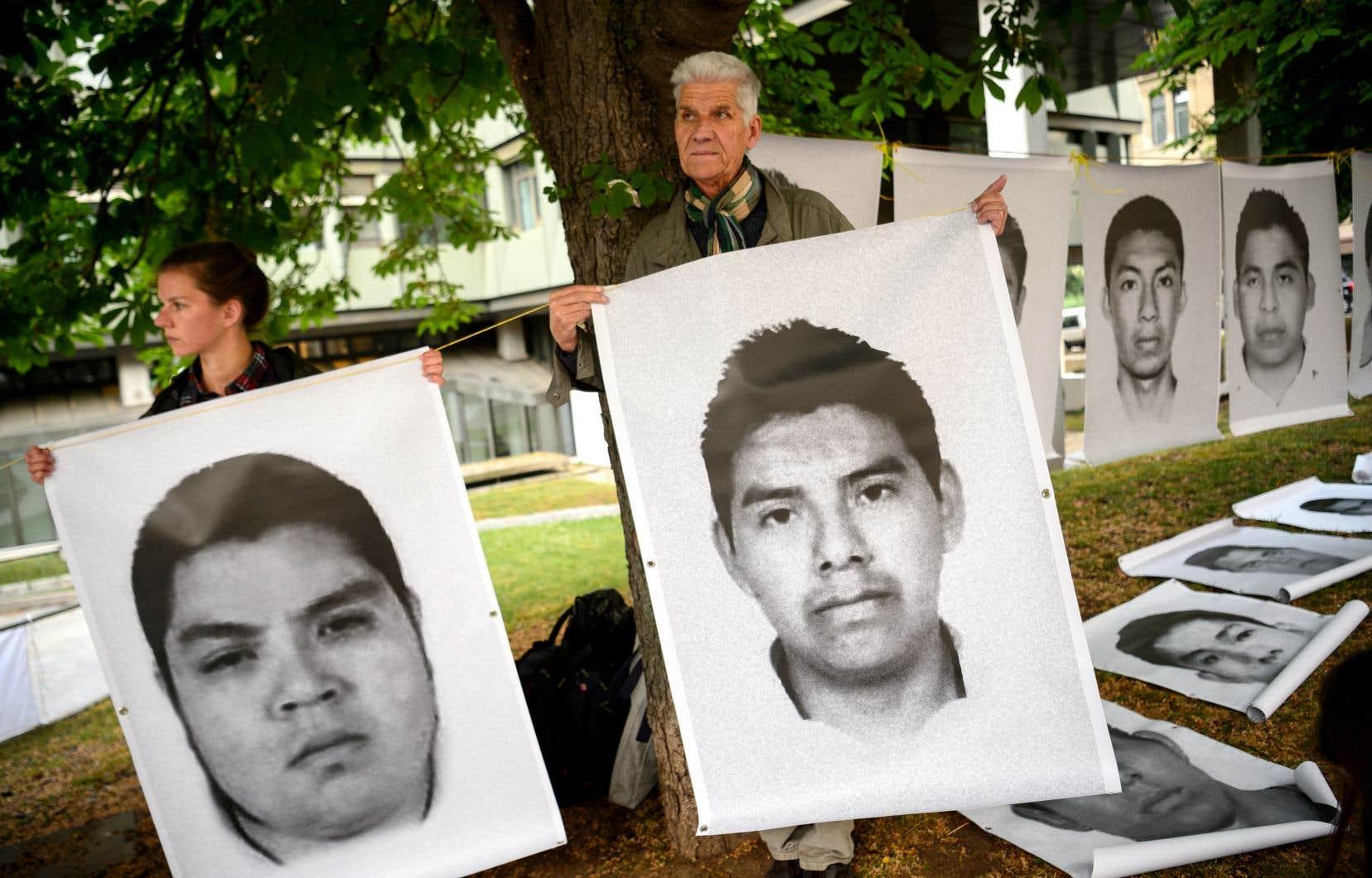 Des manifestants tenant des portraits d'étudiants tués en 2014, devant le tribunal de Stuttgart, mardi