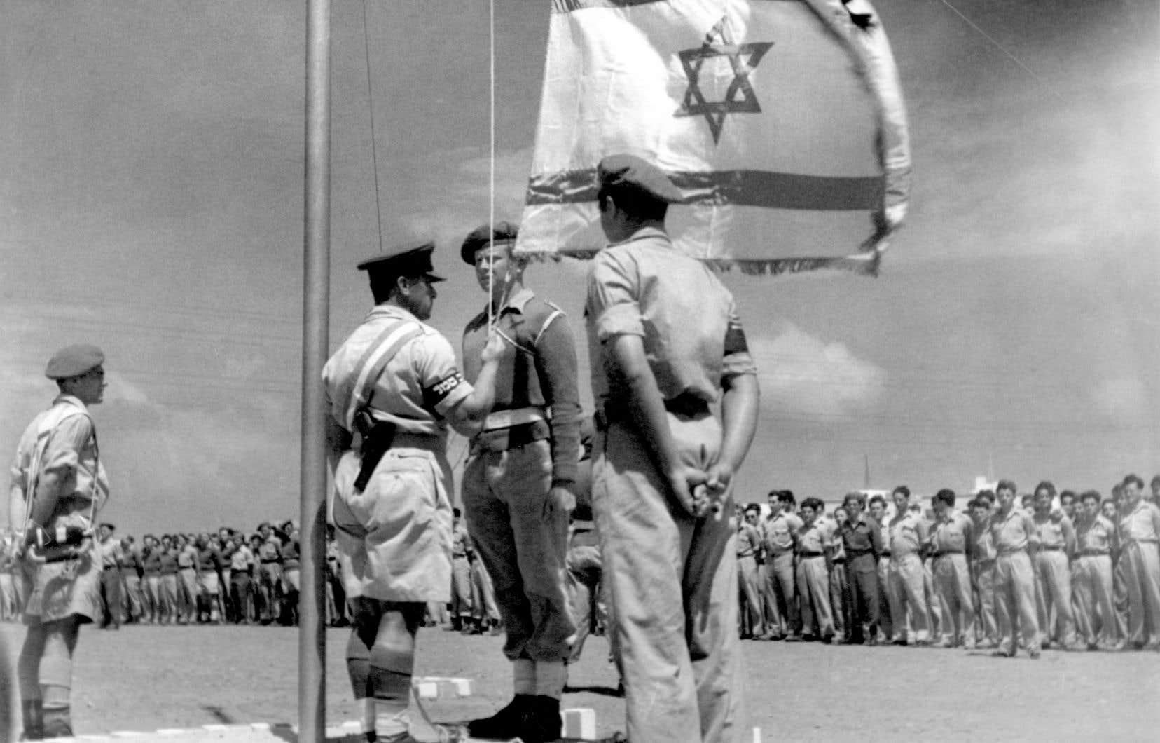Un officier israélien hisse le drapeau national pour la première fois, quelques jours après la proclamation de l'État d'Israël le 14 mai 1948.