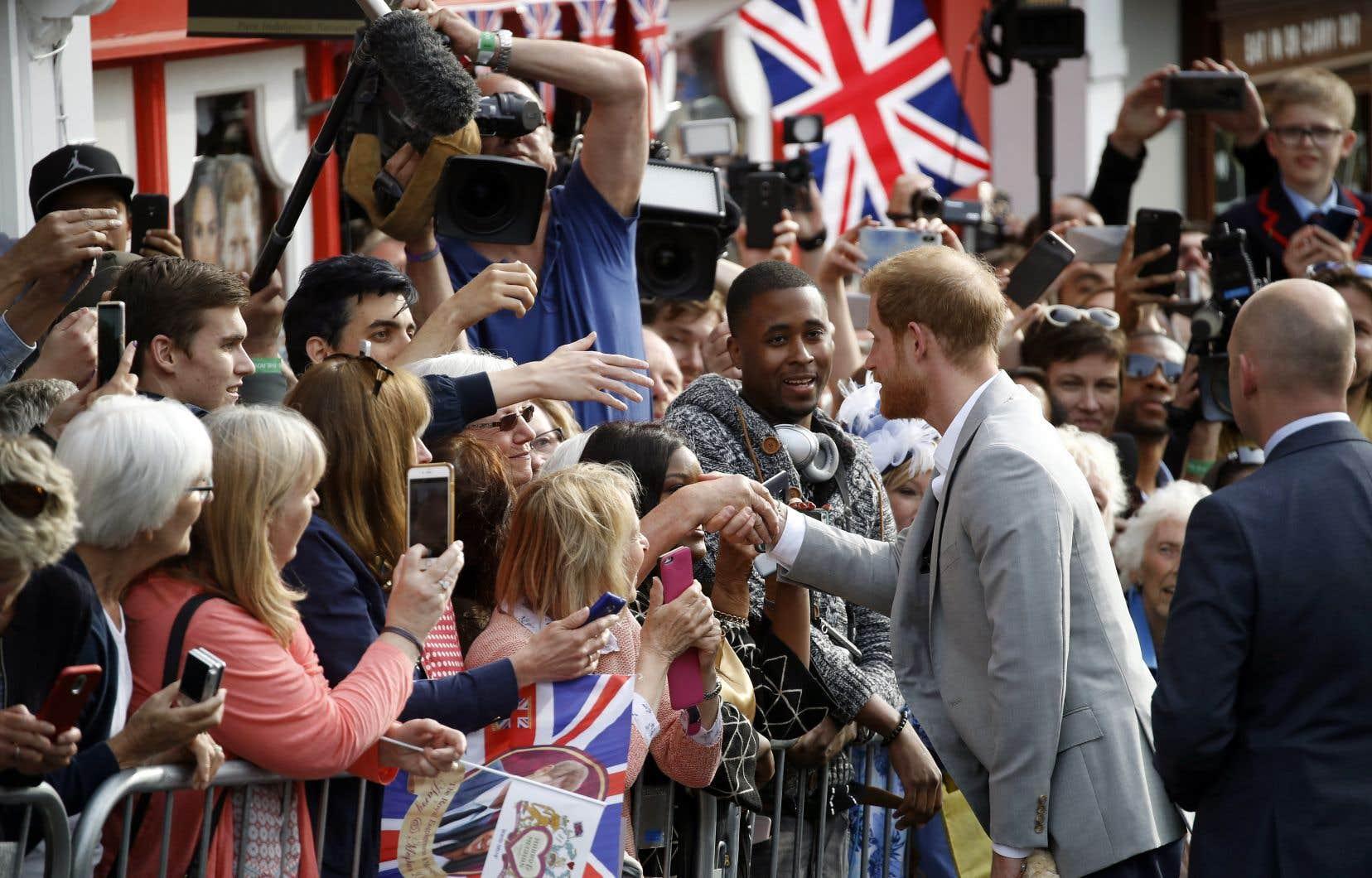 Le prince de Galles (au veston gris), Harry, a pris le temps de rencontrer des admirateurs, à la veille de son mariage avec Meghan Markle, vendredi, à Windsor.