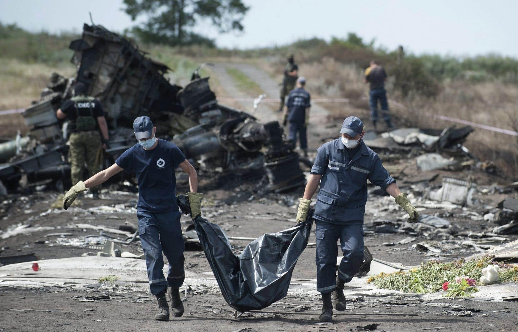 Des ambulanciers transportent le corps d'une victime de l'écrasement du vol MH17, près du village ukrainien de Hrabove, alors que des combattants pro-russes montent la garde, le 20 juillet 2014.