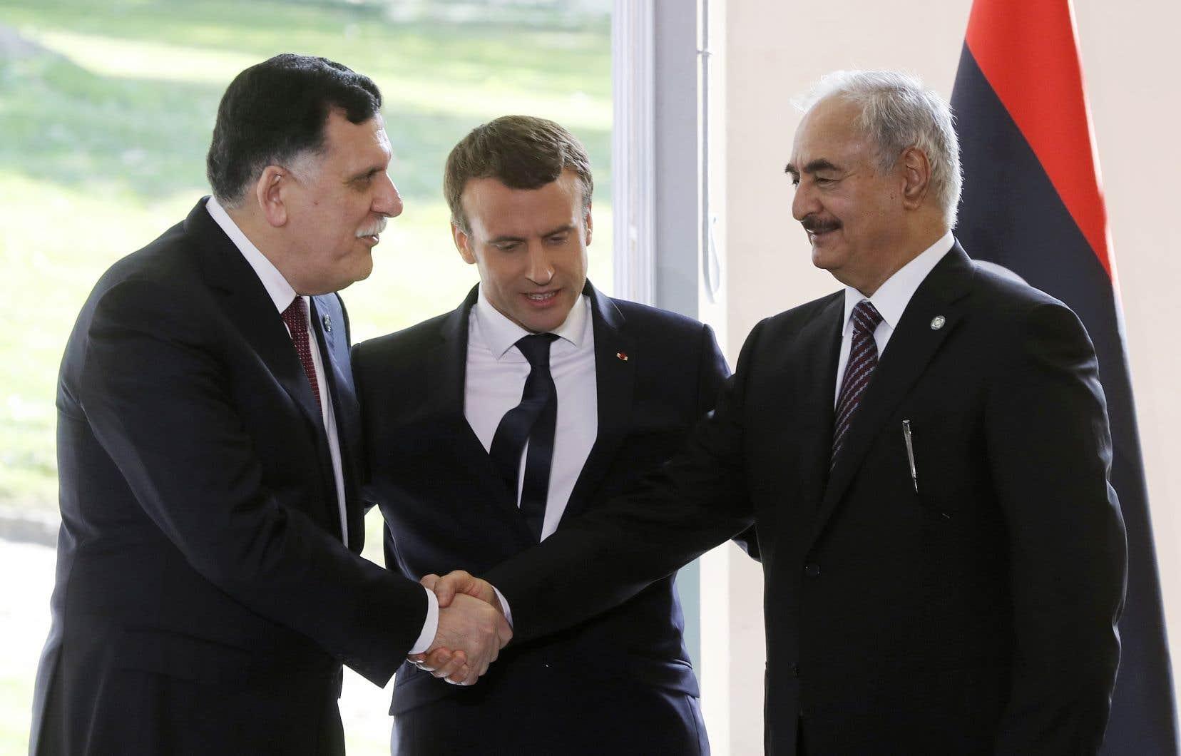 Le premier ministre libyen, Fayez al-Sarraj (à gauche), serre la main du général Khalifa Haftar, commandant de l'armée nationale libyenne, devant le président français, Emmanuel Macron, le 25 juillet 2017.