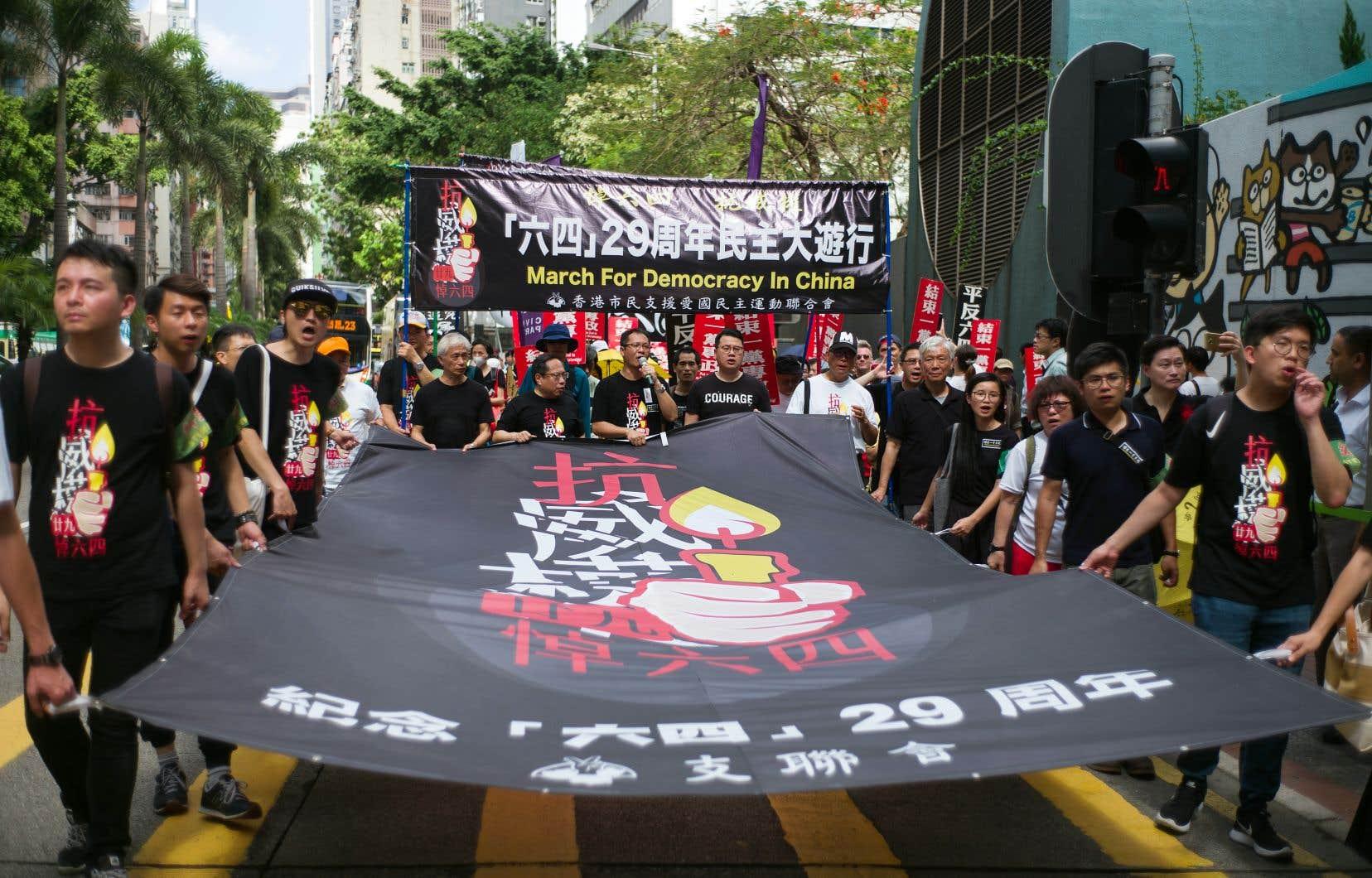 Des manifestants déambulent dans les rues du Hong Kong et brandissent une bannière intitulée «Marche pour la démocratie en Chine» dimanche.