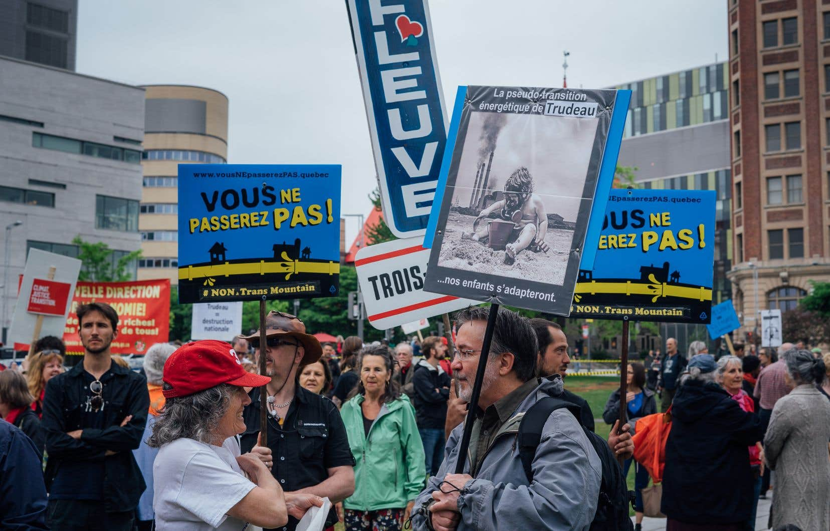 Abrités sous des parapluies qui s'ouvraient et se fermaient au gré de l'intensité de l'averse, les manifestants ont écouté des discours, des prières et des chants de représentants d'organisations environnementales, de nations autochtones, de syndicats du Québec et autres mouvements sociaux.