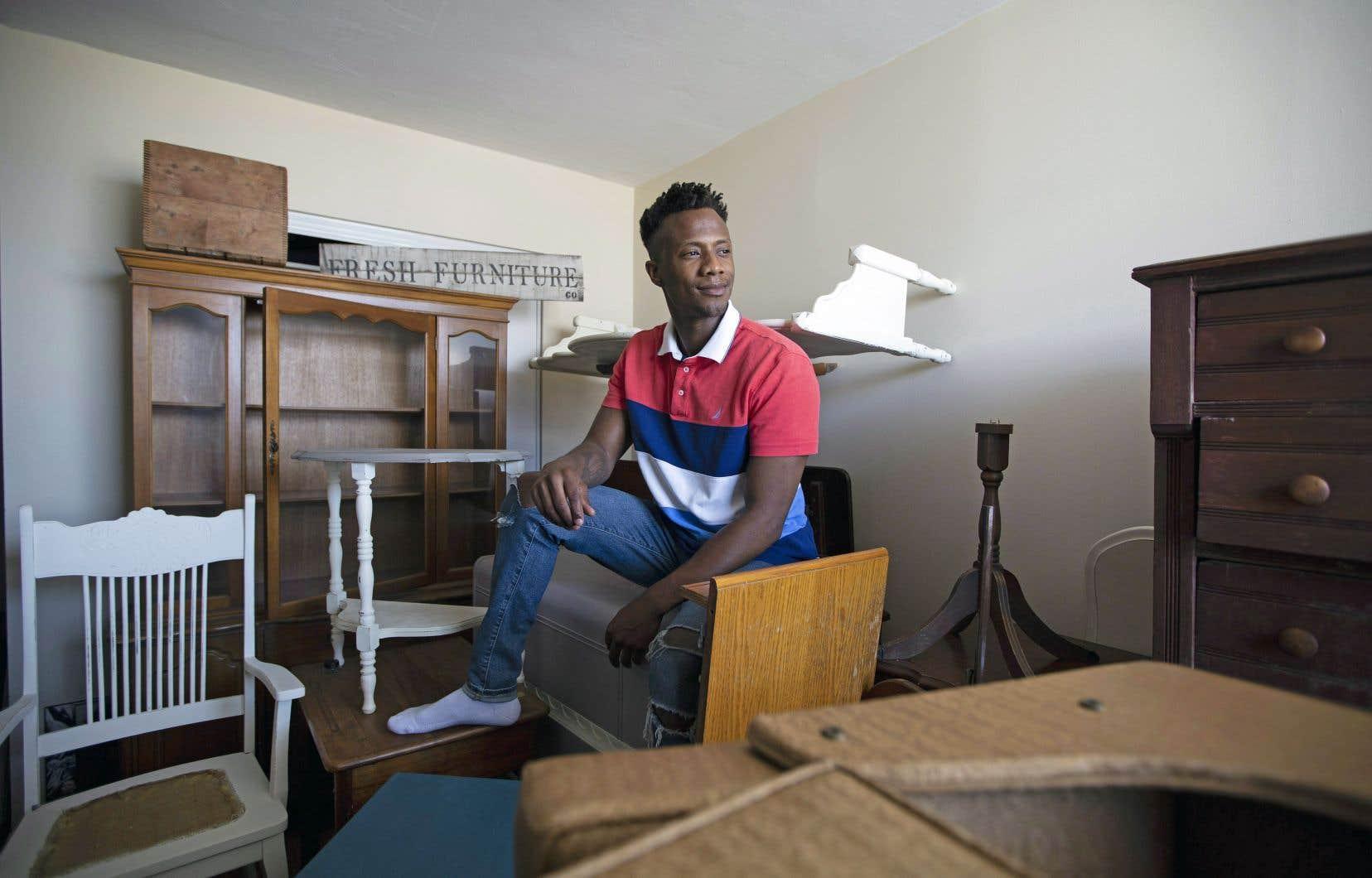 Kbre Hamilton, entouré de meubles dans son appartement de Hamilton, en Ontario