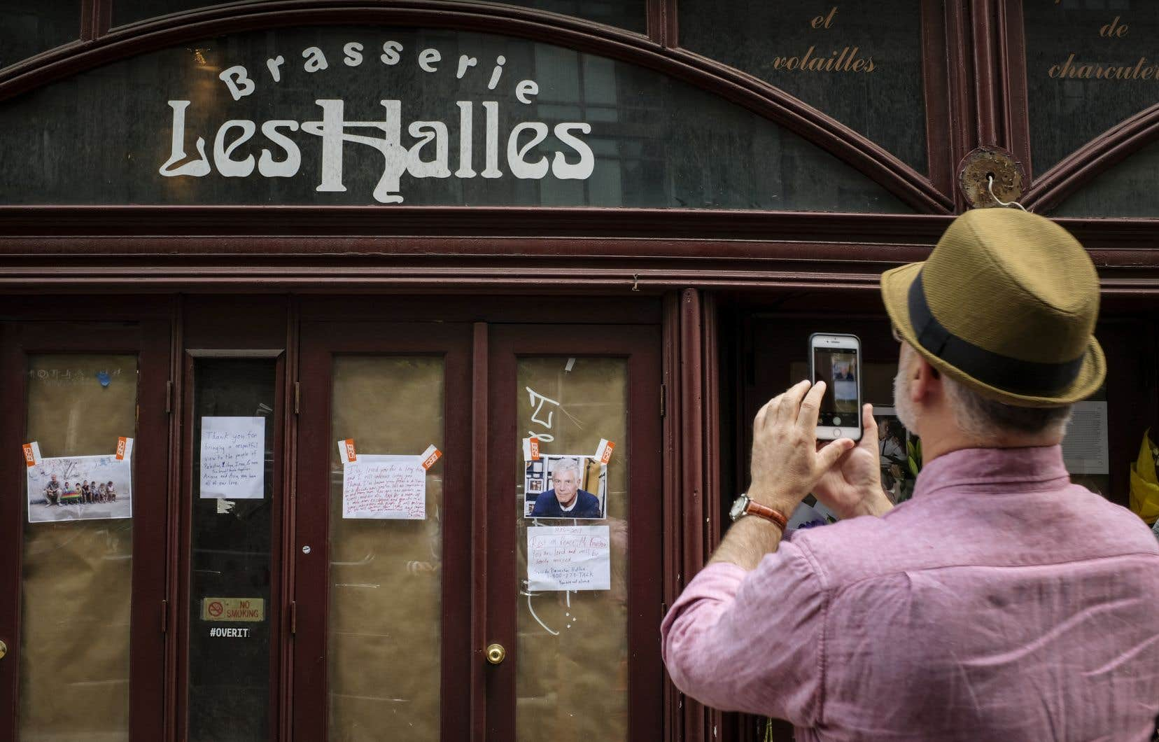 Des passants se recueillent devant la célèbre brasserie Les Halles, à New York, où Anthony Bourdain s'est fait connaître.