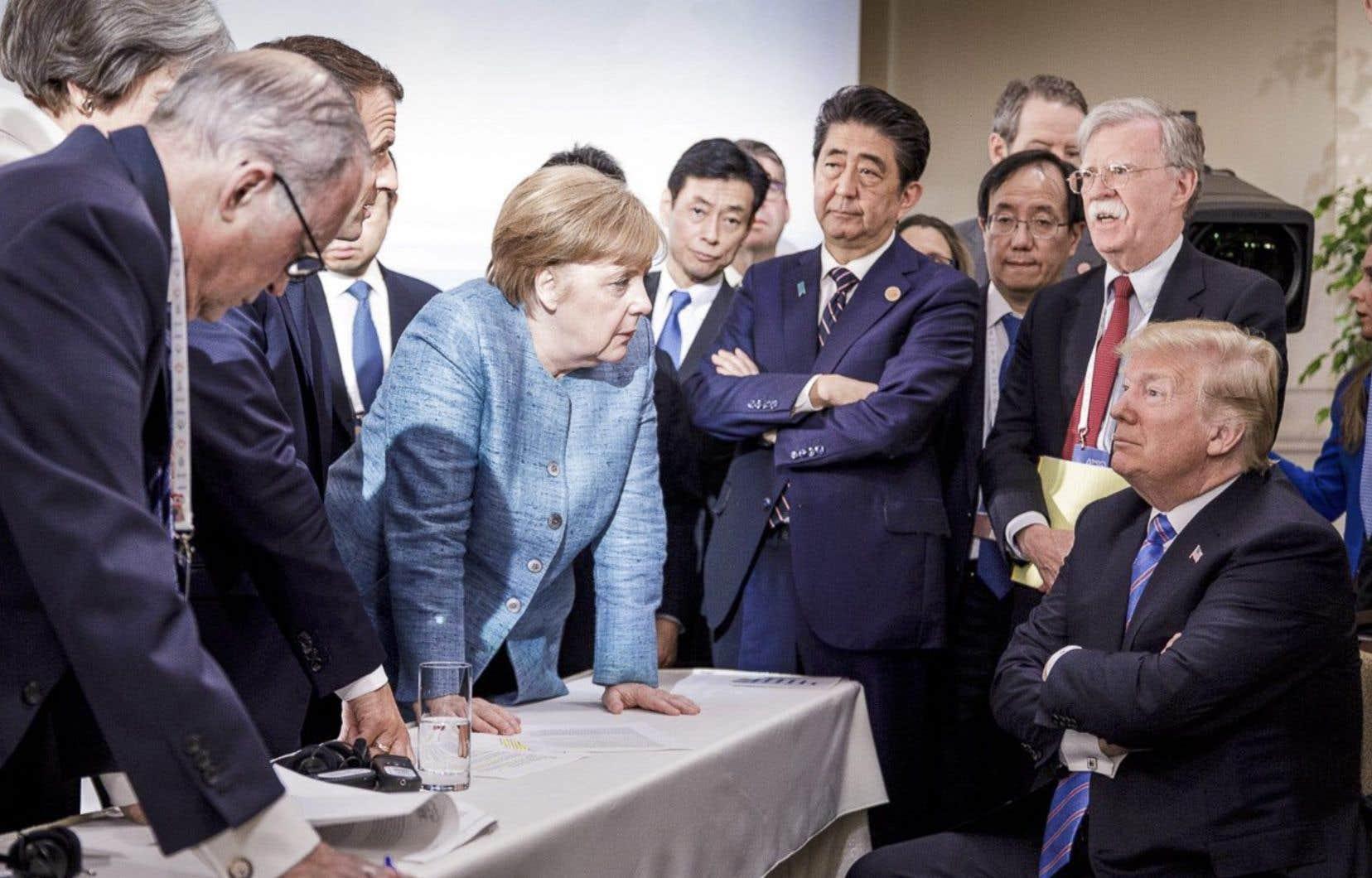 Dans cette image divulguée par le gouvernement allemand, la chancelière Angela Merkel s'adresse au président Donald Trump, assis, lors du sommet du G7 à La Malbaie, samedi.