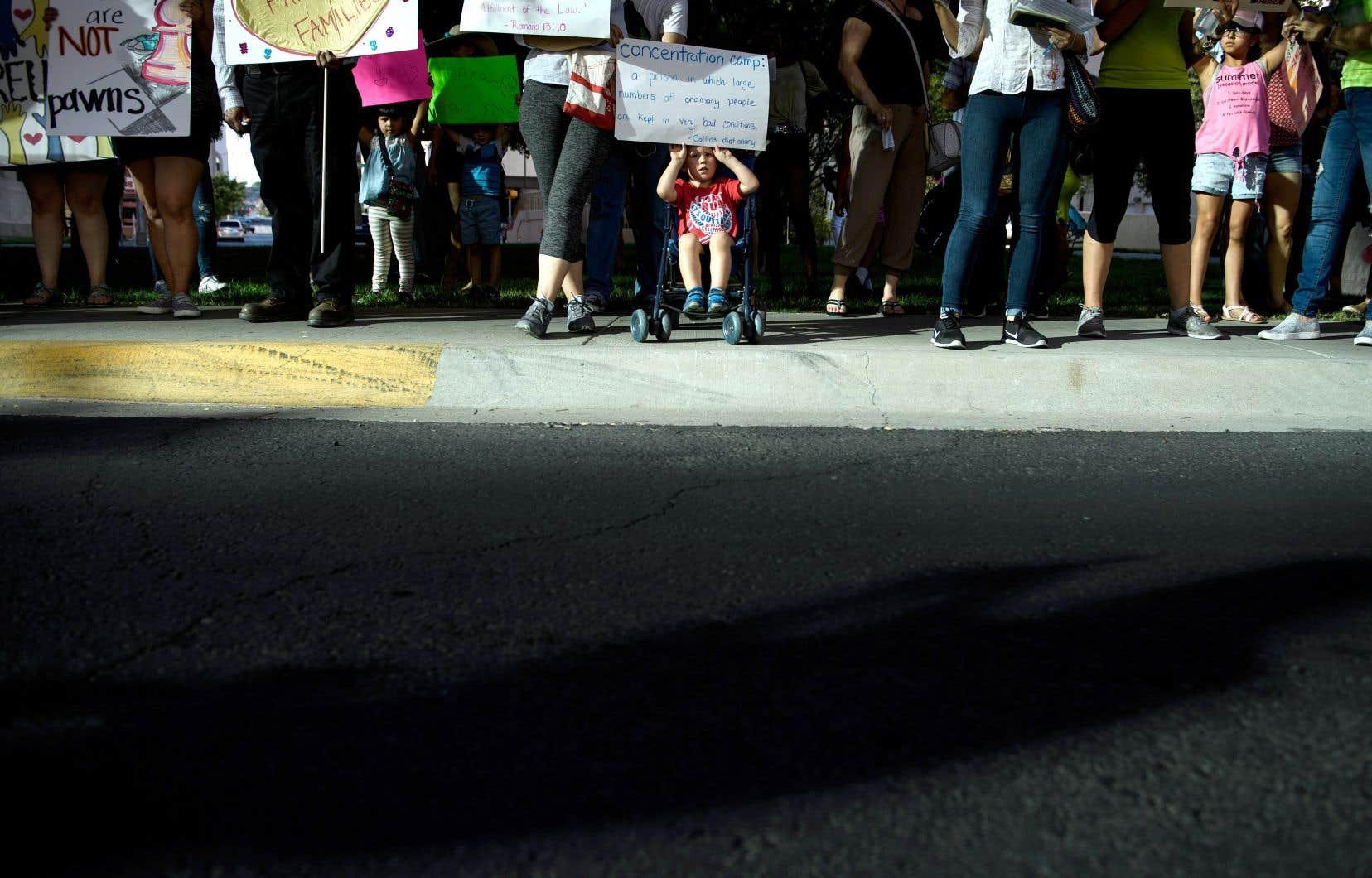 Devant un centre de détention au Texas, un enfant, installé dans une poussette, tient au-dessus de sa tête une pancarte manifestant son opposition à la séparation des familles immigrantes.