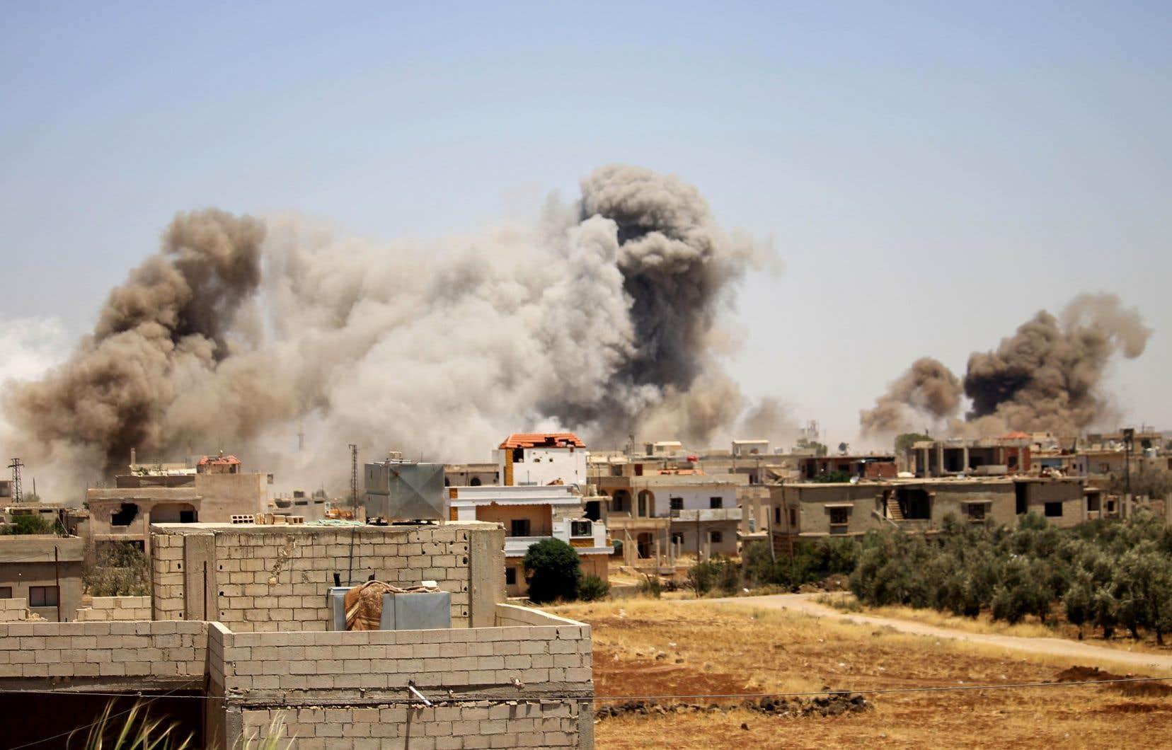 Une épaisse fumée s'élève au-dessus dela ville de Busra al-Harir, dans la province de Deraa, à la suite de raids aériens dimanche.