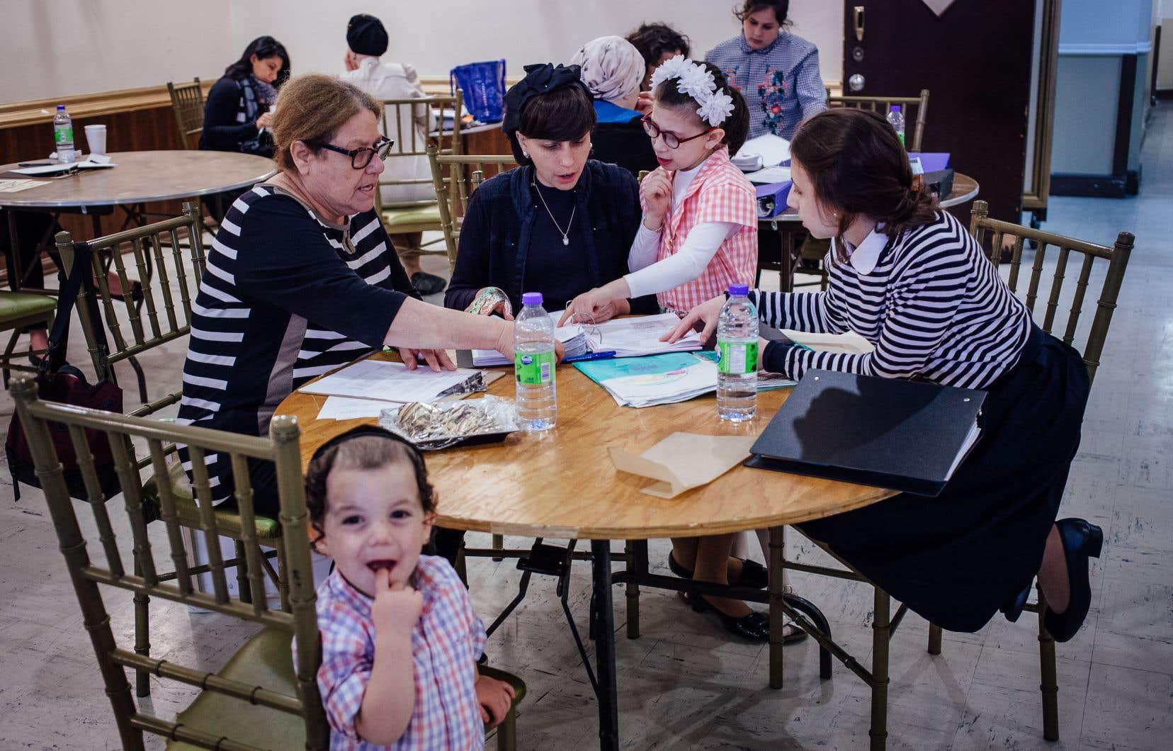 Rachelle Kahan, mère de 14 enfants, présente à l'évaluatrice Bev Miller (à gauche) les cartables de ses enfants à qui elle enseigne à la maison.