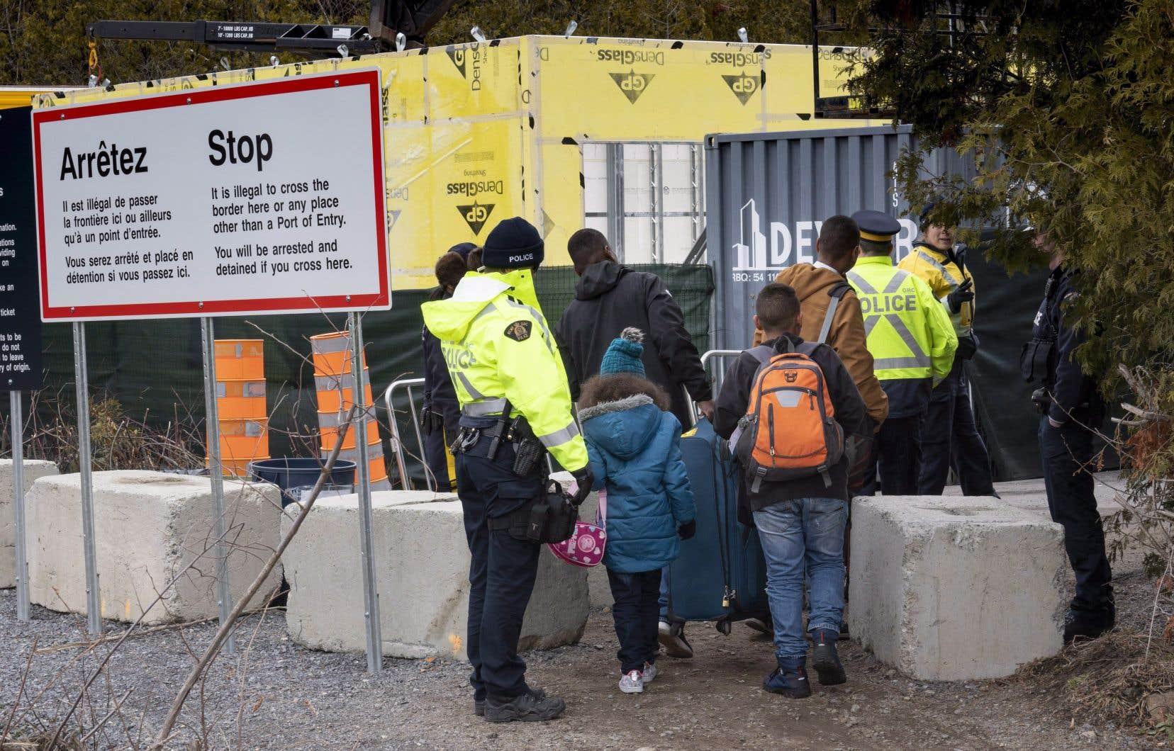 Des policiers interceptant une famille de migrants sur le chemin Roxham, en avril dernier