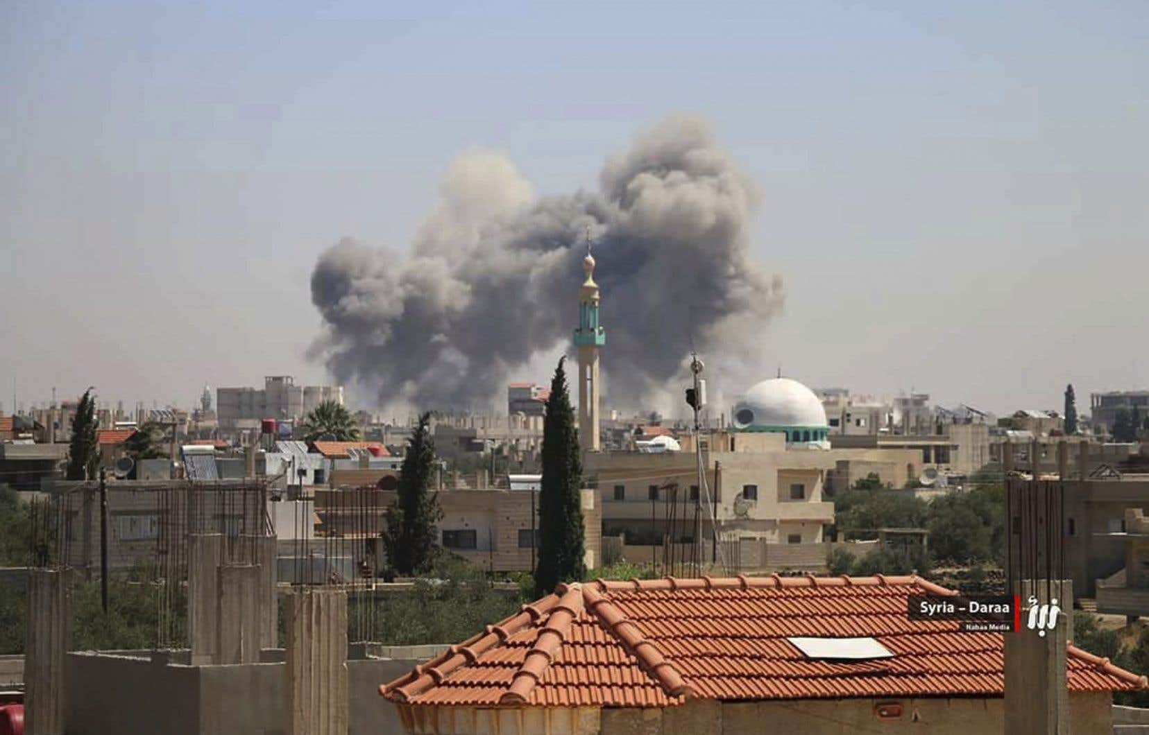 Cette photo fournie par Nabaa Media, un média syrien de l'opposition, montre de la fumée qui s'échappe des bâtiments touchés par les bombardements des forces gouvernementales syriennes, jeudi, dans la province de Deraa.