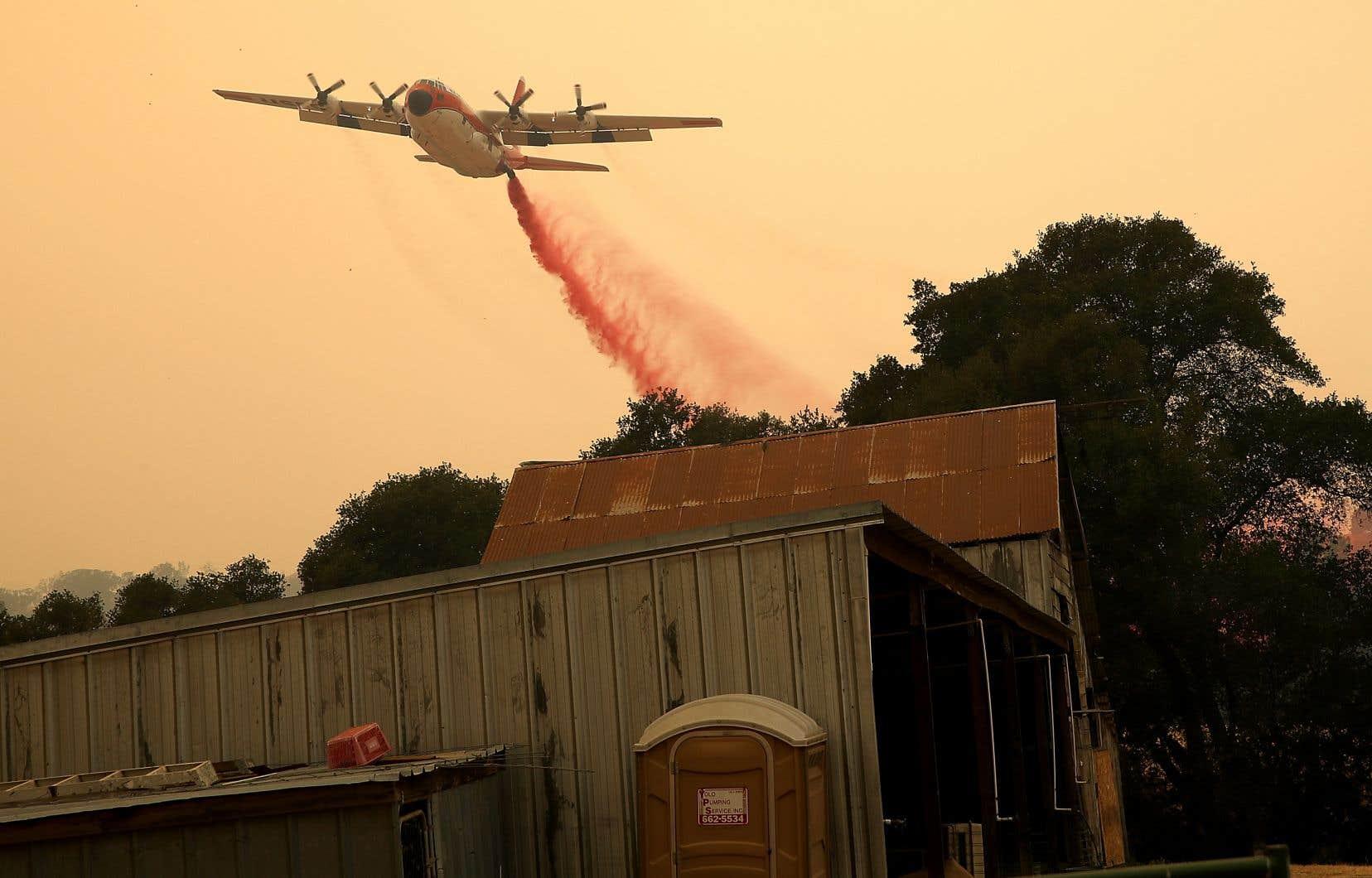 Un avion de lutte contre les incendies lance un retardateur de feu près d'une structure dansle «County Fire» à Esparto, en Californie.