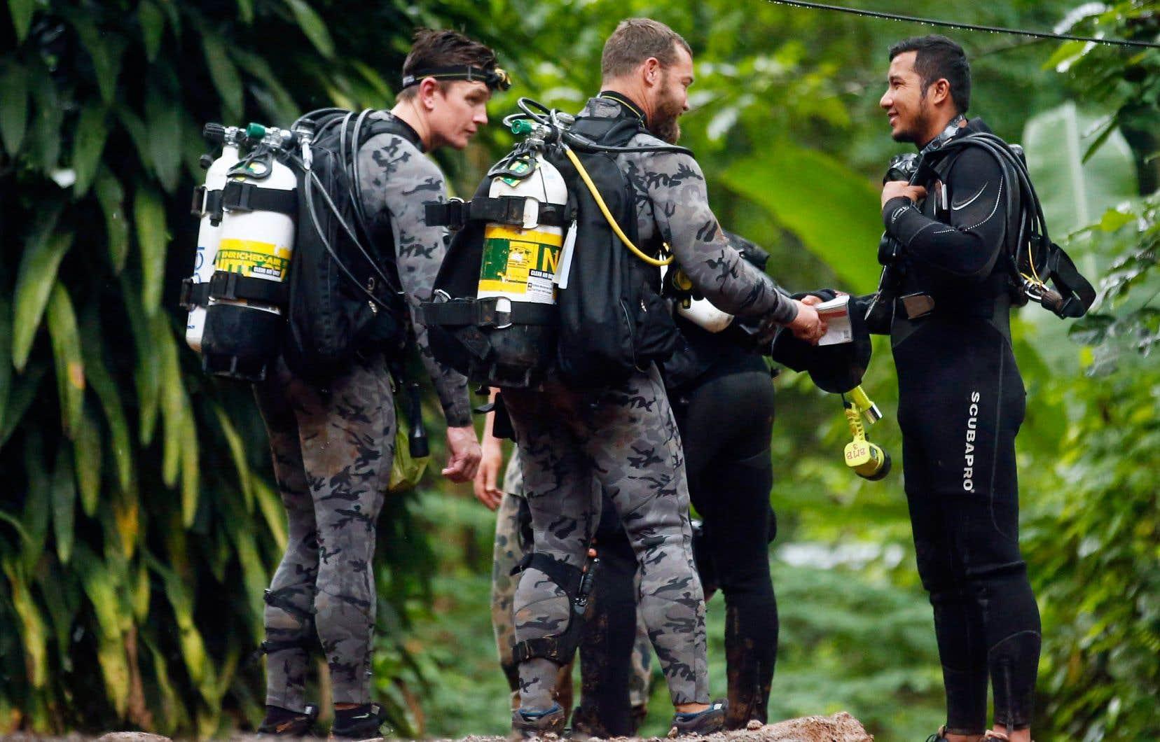 Des membres de la police fédérale australienne discutent avec un secouriste thaïlandais.
