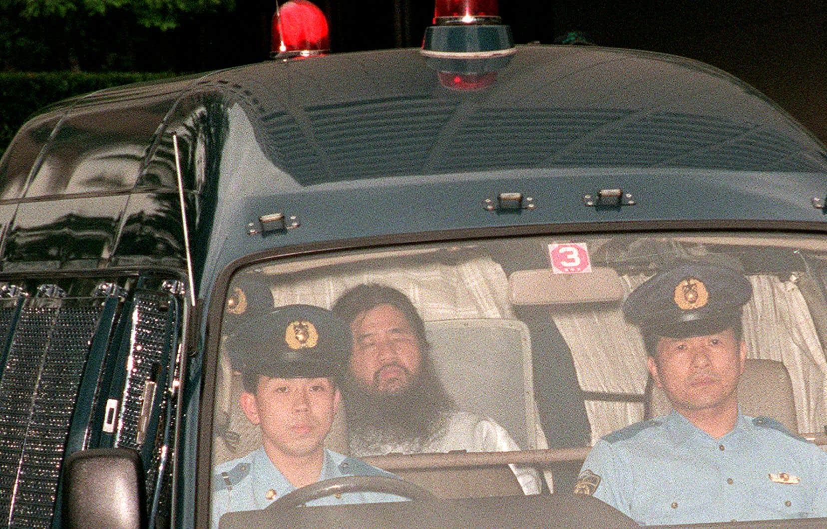 Shoko Asahara escorté par des policiers en juillet 1995