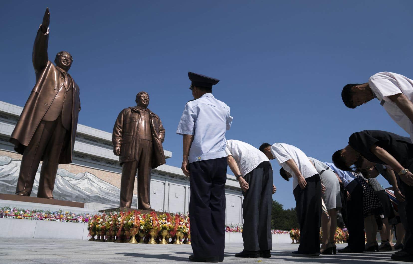Des Nord-Coréens rendent hommage aux statues de bronze des défunts dirigeants Kim Il-sung (à gauche) et Kim Jong-il, à Pyongyang le 7 juillet 2018.