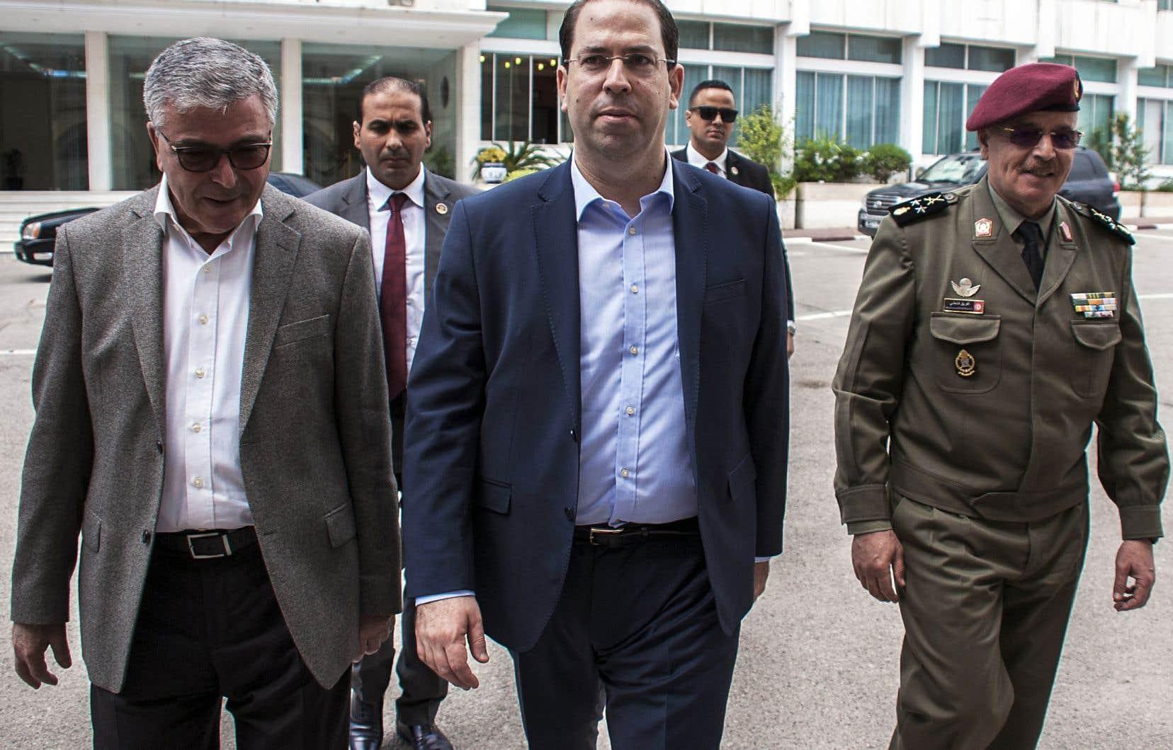 Le premier ministre tunisien, Youssef Chahed (au centre), aux côtés de son ministre de la Défense, Abelkarim Zebidi (à gauche), à Tunis, en mai dernier