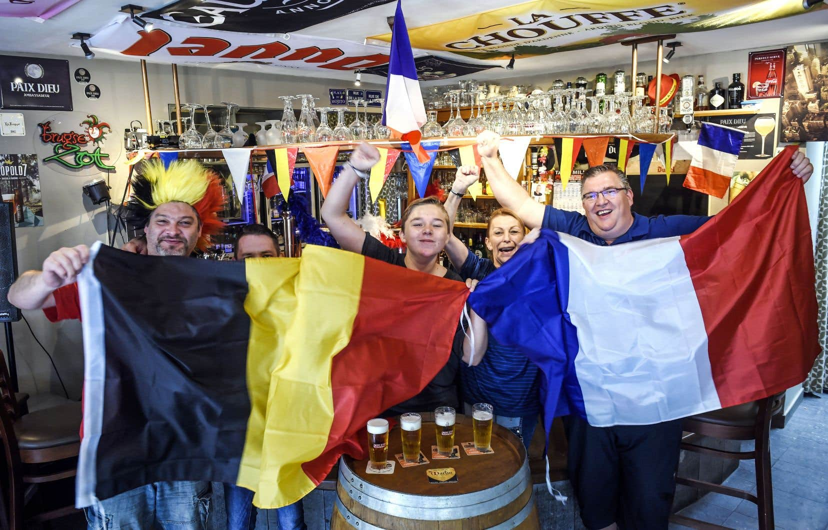 Des partisans affichent amicalement leurs couleurs, la veille du match qui opposera la Belgique à la France en demi-finale de la Coupe du monde.