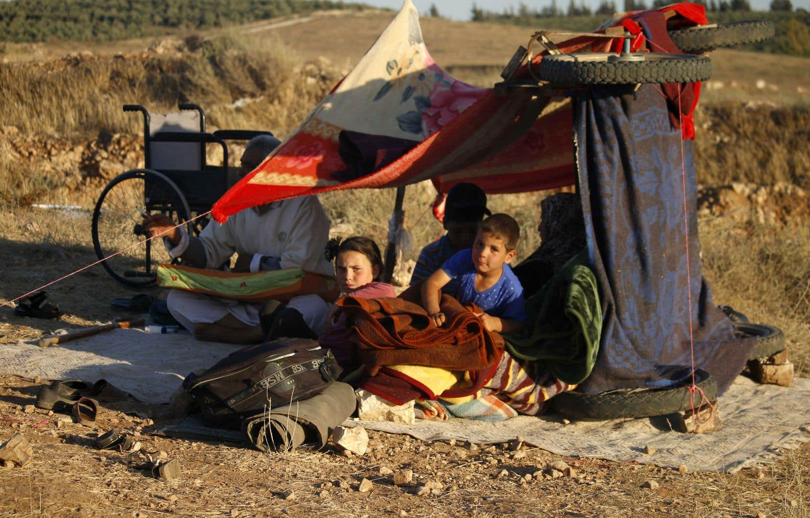 Des Syriens fuyant la province de Deraa attendent dans un camp de fortune aux abords de la frontière jordanienne.
