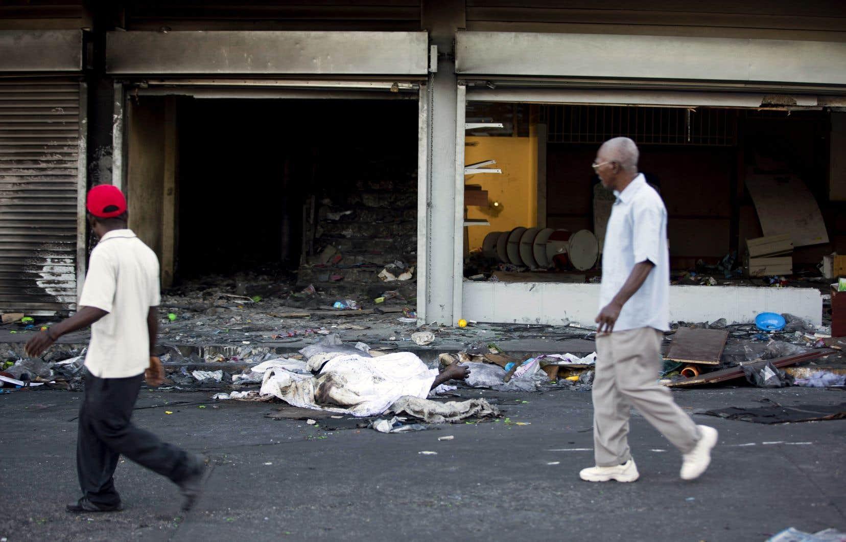 Deux corps recouverts d'un drap restent dans la rue devant un magasin pillé et incendié au cours des émeutes qui ont éclaté samedi à Port-au-Prince.