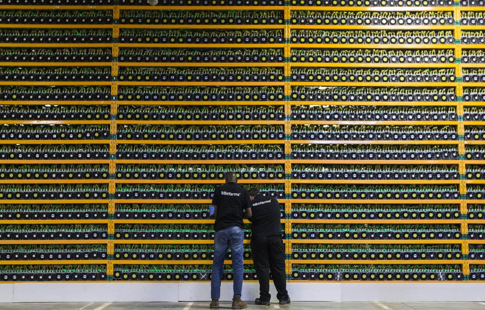 Des techniciens assurent le bon fonctionnement d'une mine de Bitcoin, en Montérégie.