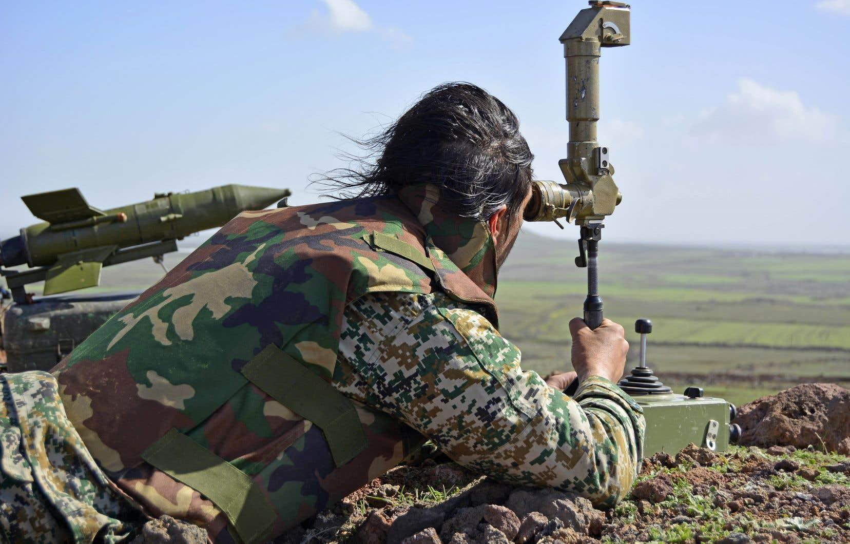 Un membre des troupes de Bachar al-Assad scrute les positions rebelles au nord de la ville syrienne de Deraa, en mars 2015.