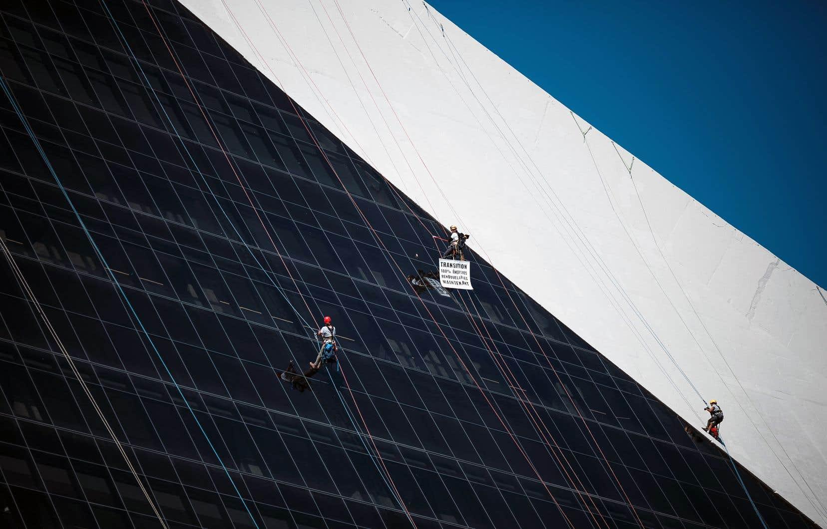 Les militants de Greenpeace ont escaladé une partie de la tour du Stade olympique avant de déployer leur bannière.