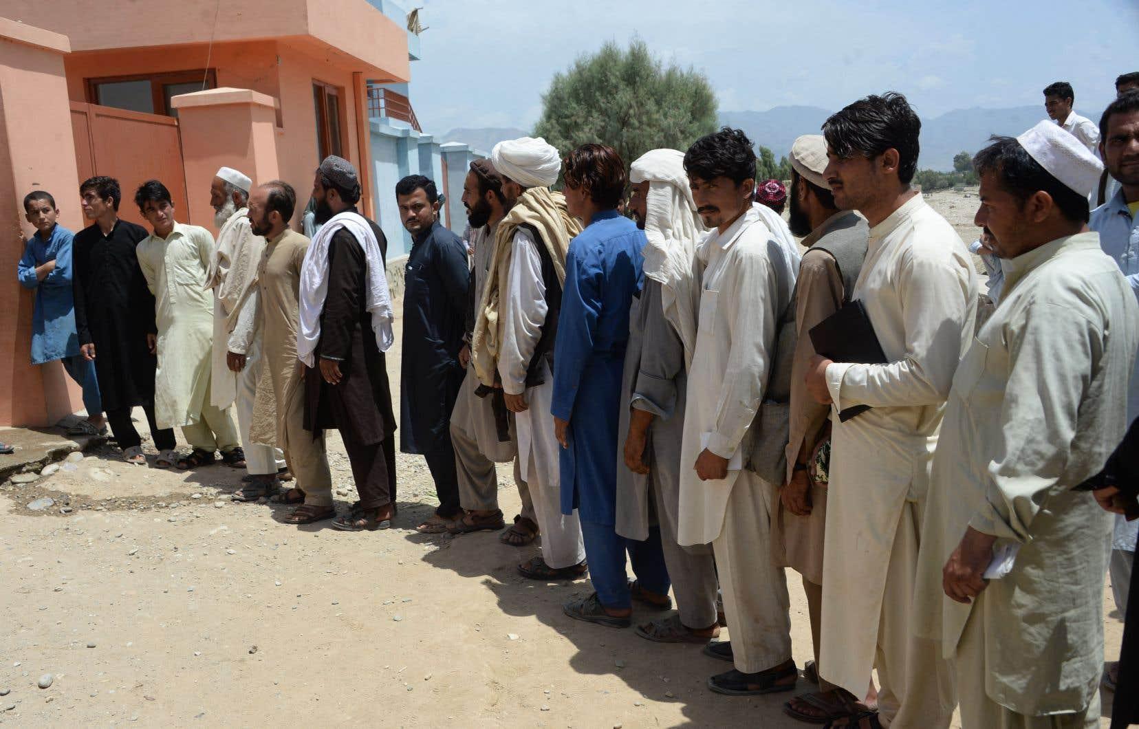 Des hommes afghans s'inscrivent pour participer aux prochaines élections parlementaires, dans le district de Bihsood.