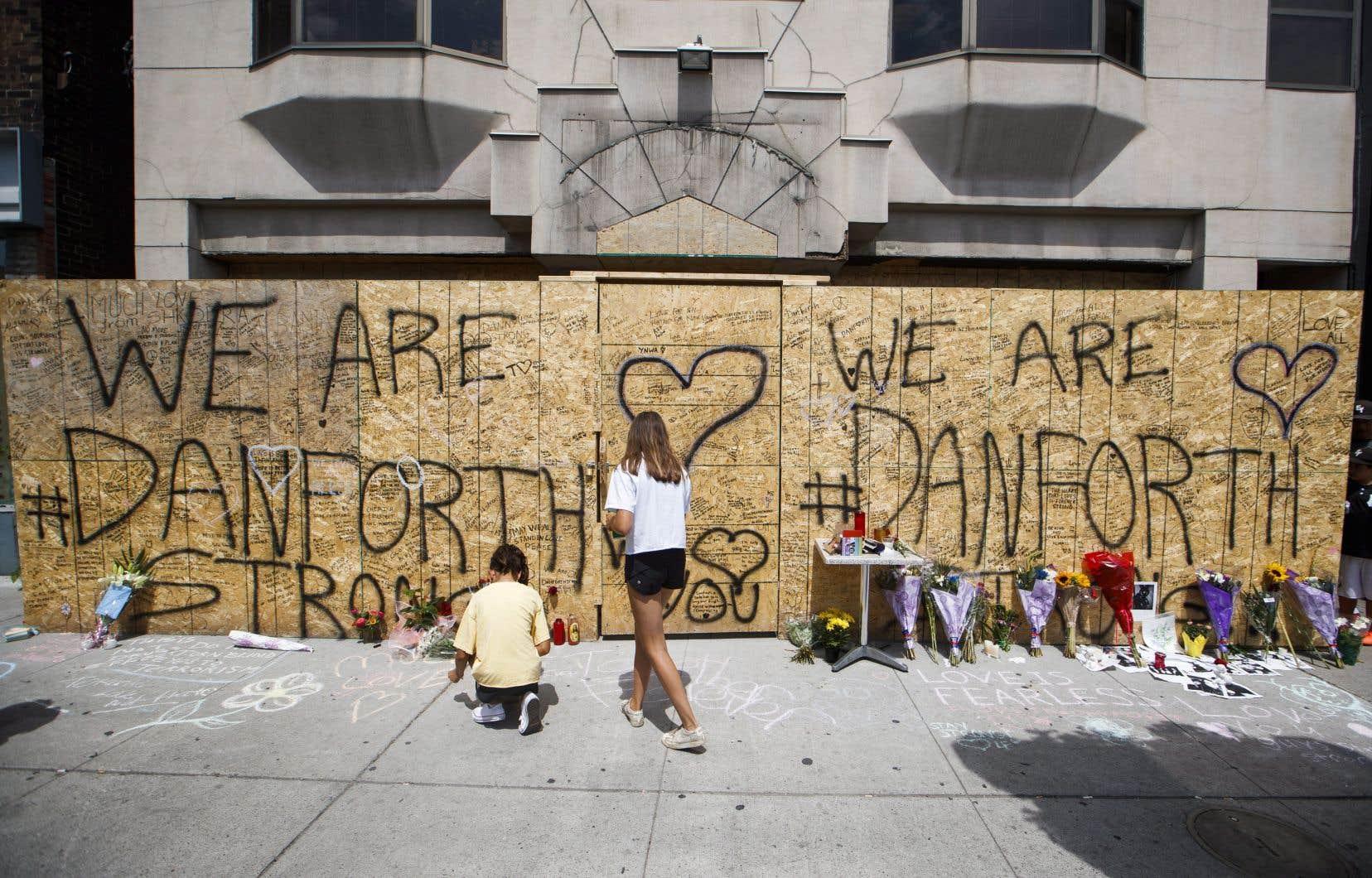 Des passants écrivent des messages sur un monument commémoratif improvisé en l'honneur des victimes de la fusillade de dimanche soir sur l'avenue Danforth.