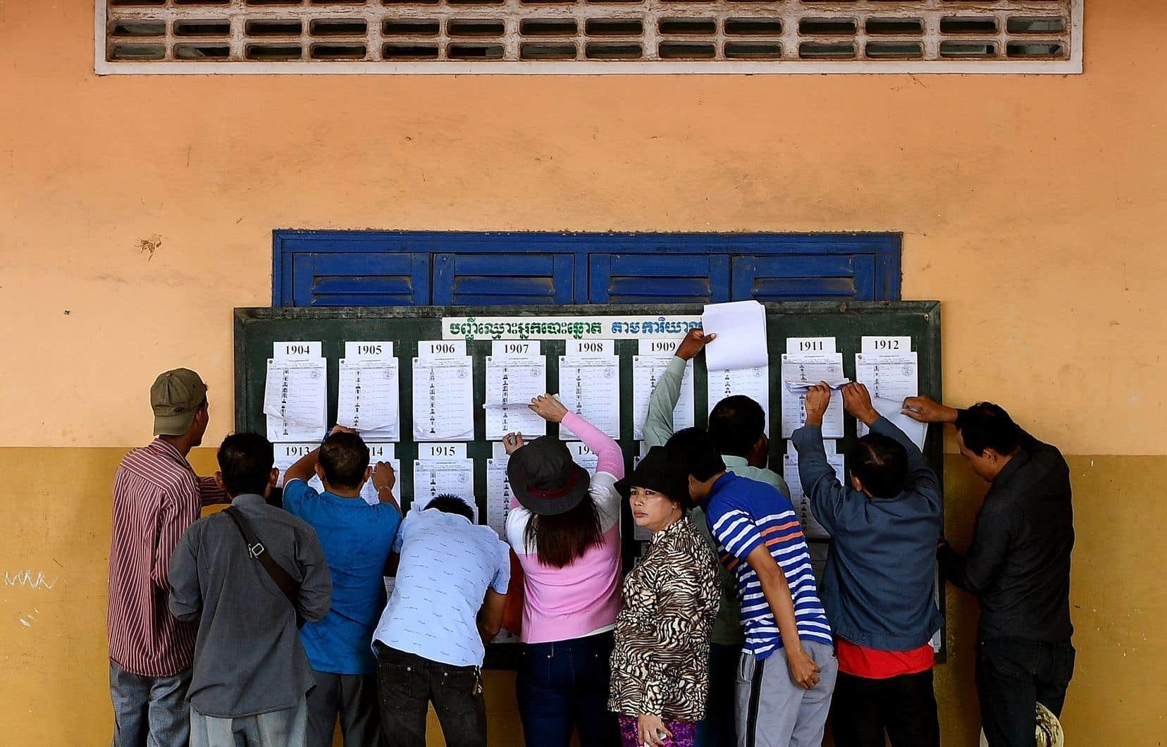 Des Cambodgiens cherchent leur nom sur une liste électorale à un bureau de vote de Phnom Penh, dimanche. Une des questions clés du scrutin concerne le taux d'abstention alors que l'opposition a appelé au boycottage des législatives.