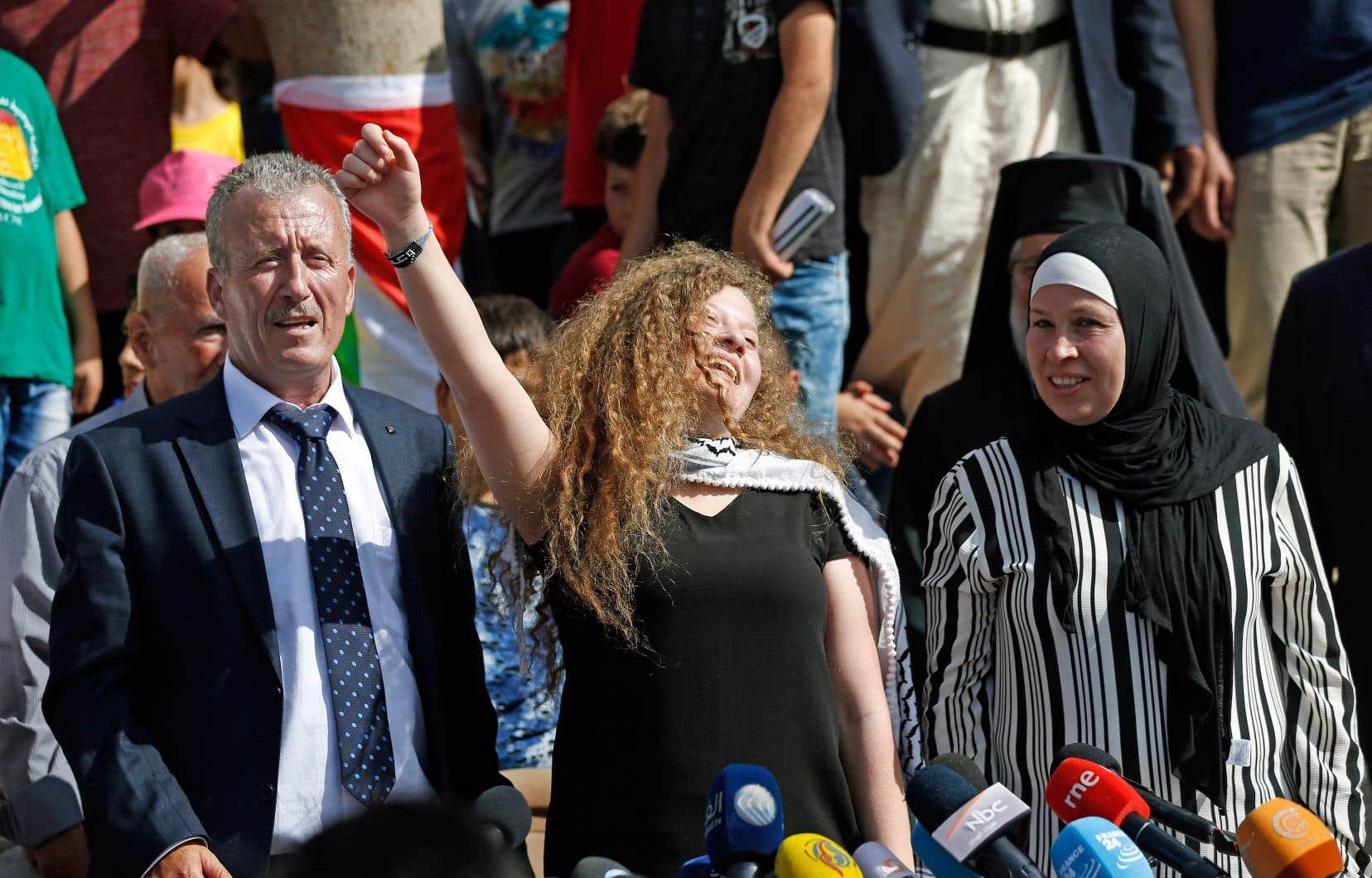 Entourée de ses parents, la militante palestinienne brandit le poing lors de la conférence de presse qu'elle a donnée après sa libération de prison, à Nabi Saleh, en Cisjordanie occupée, dimanche.