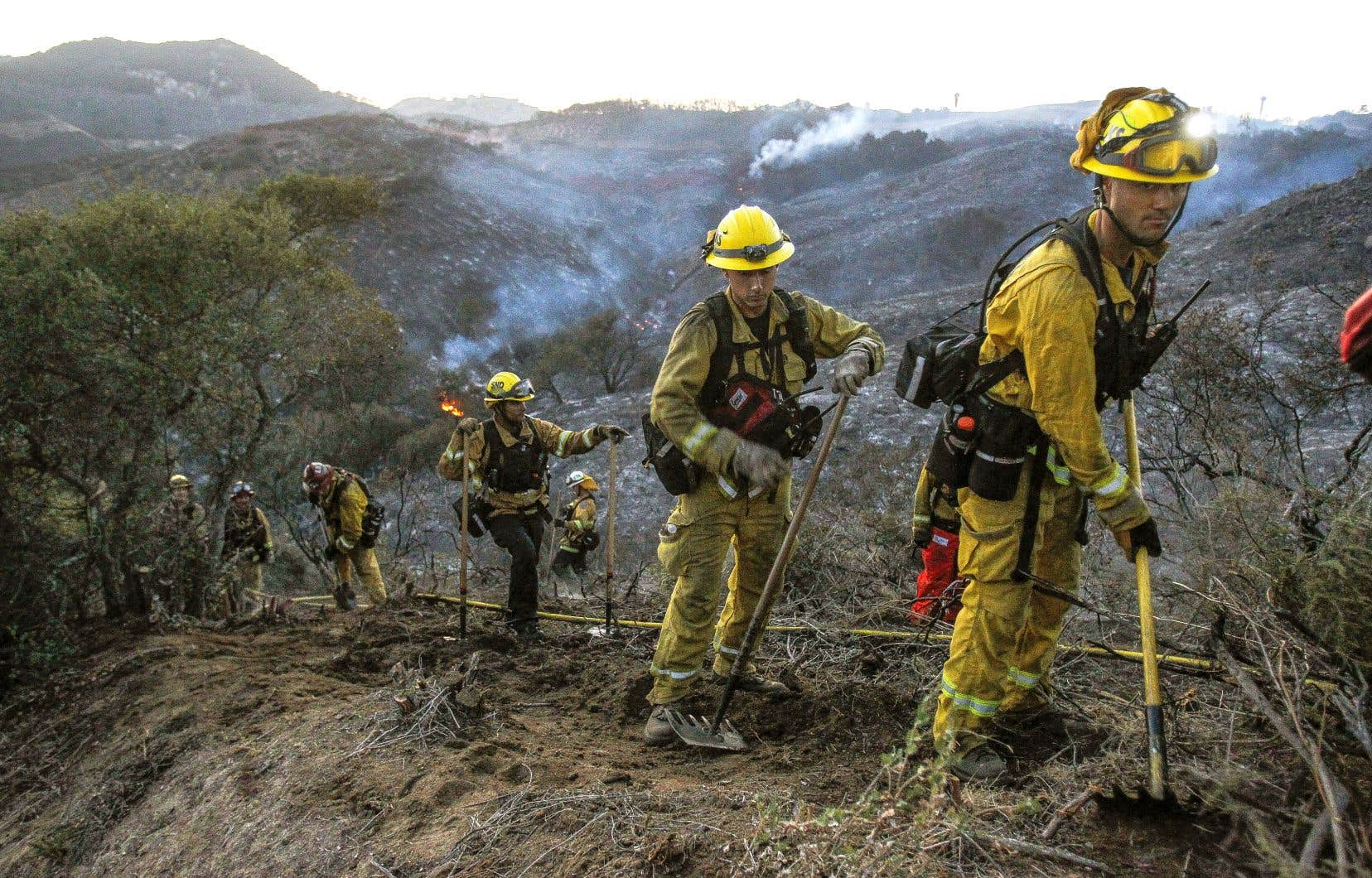 Des pompiers du comté de San Diego, en Californie, aménageant un pare-feu à De Luz, samedi