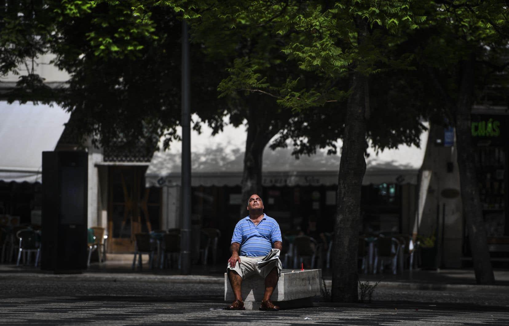 Un homme est assis sur un banc au soleil sur la place Rossio à Lisbonne le 3 août 2018.