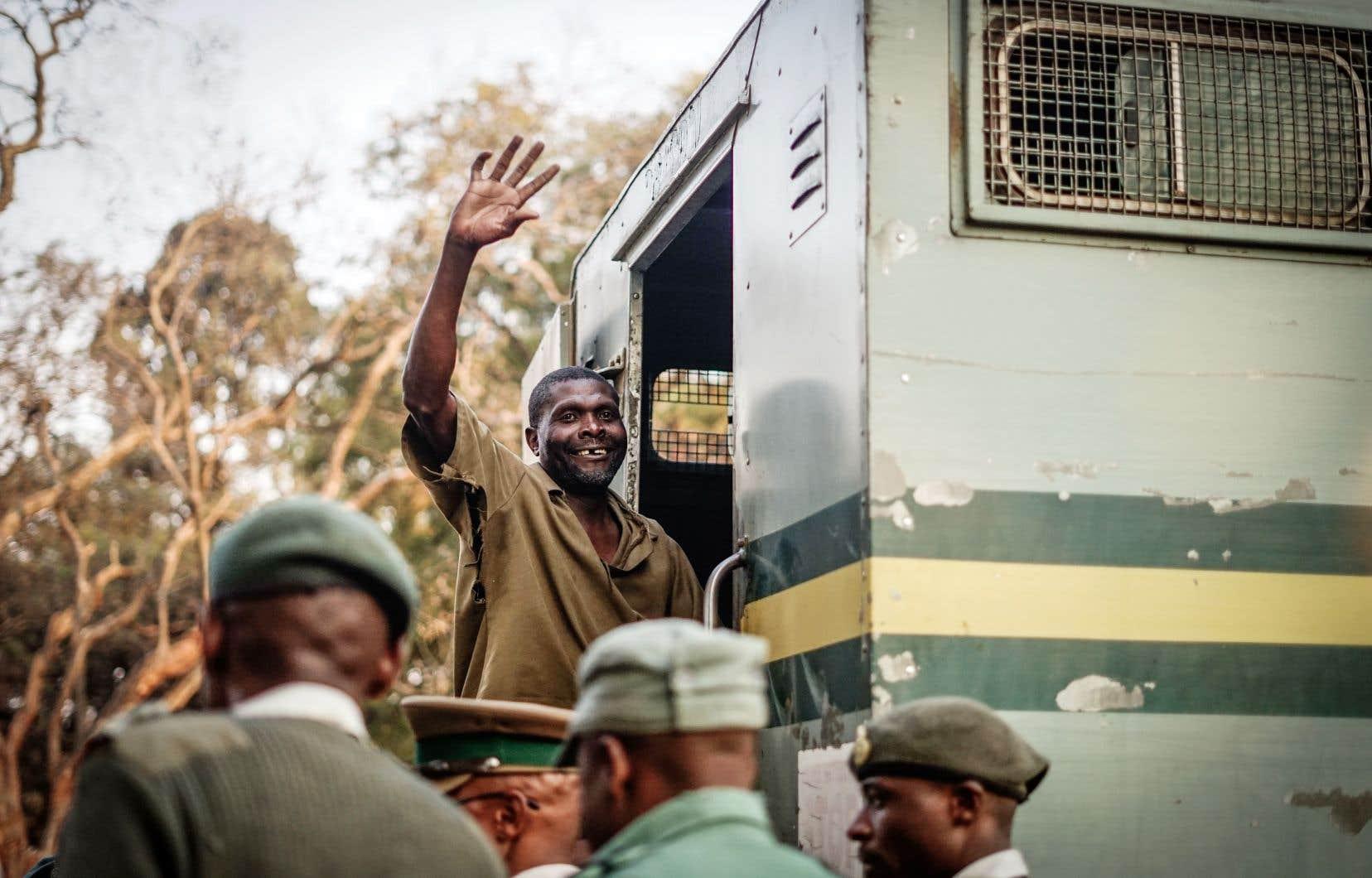 Un partisan du Mouvement pour le changement démocratique fait le geste symbolique de son parti alors qu'il est escorté du palais de justice à un camion de la police.