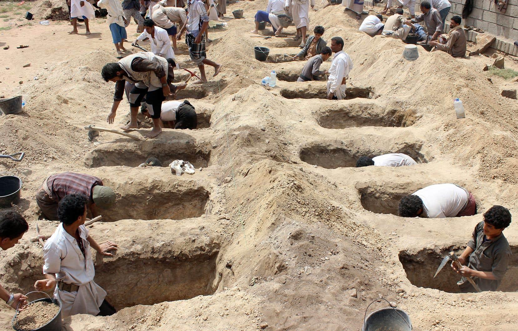 Des Yéménites creusent des tombes les unes à côté des autres en prévision de l'inhumation des enfants tués.