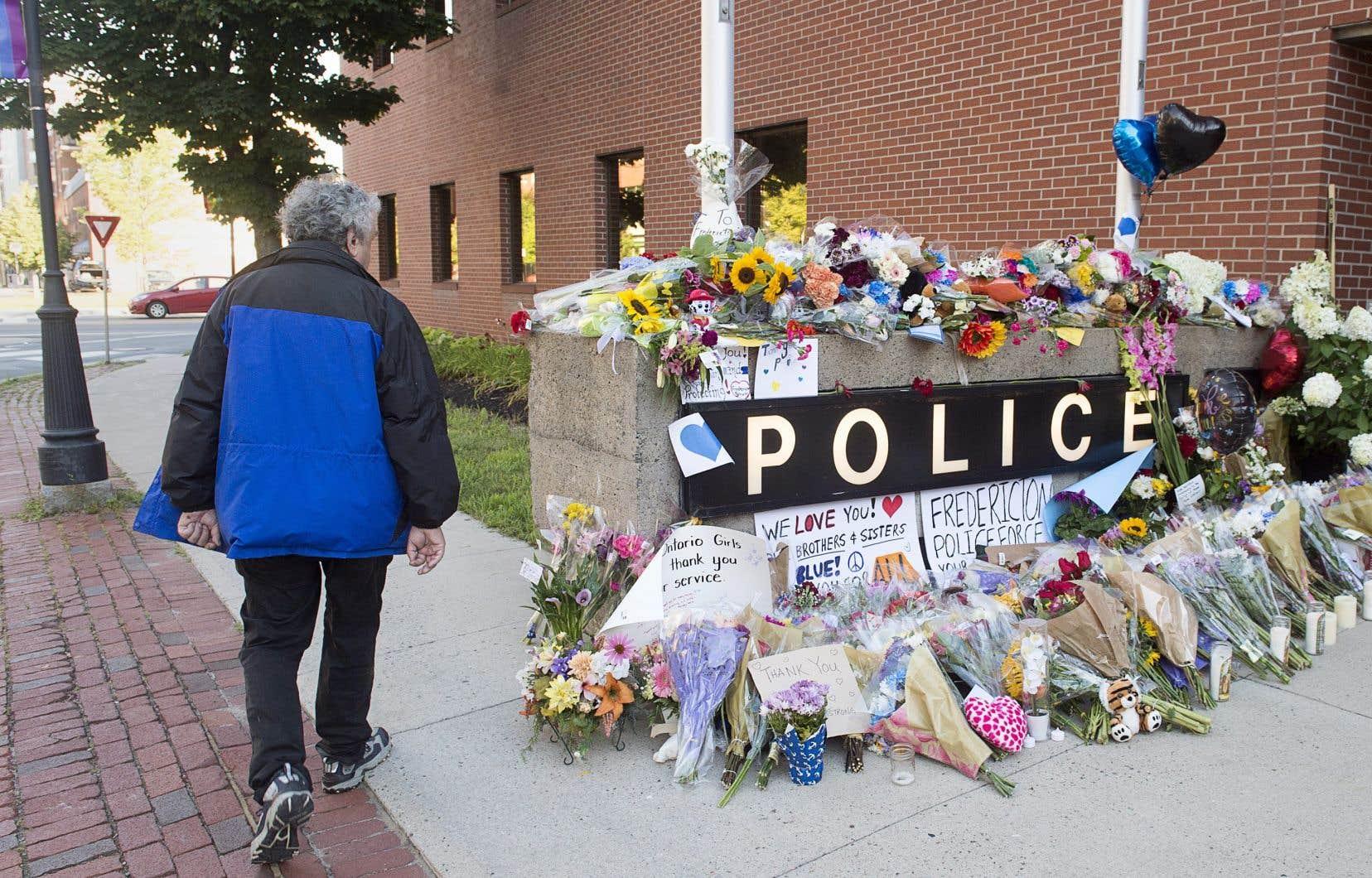 Un résident de Fredericton passe devant un hommage improvisé devant le poste de police de Fredericton le samedi 11 août 2018.