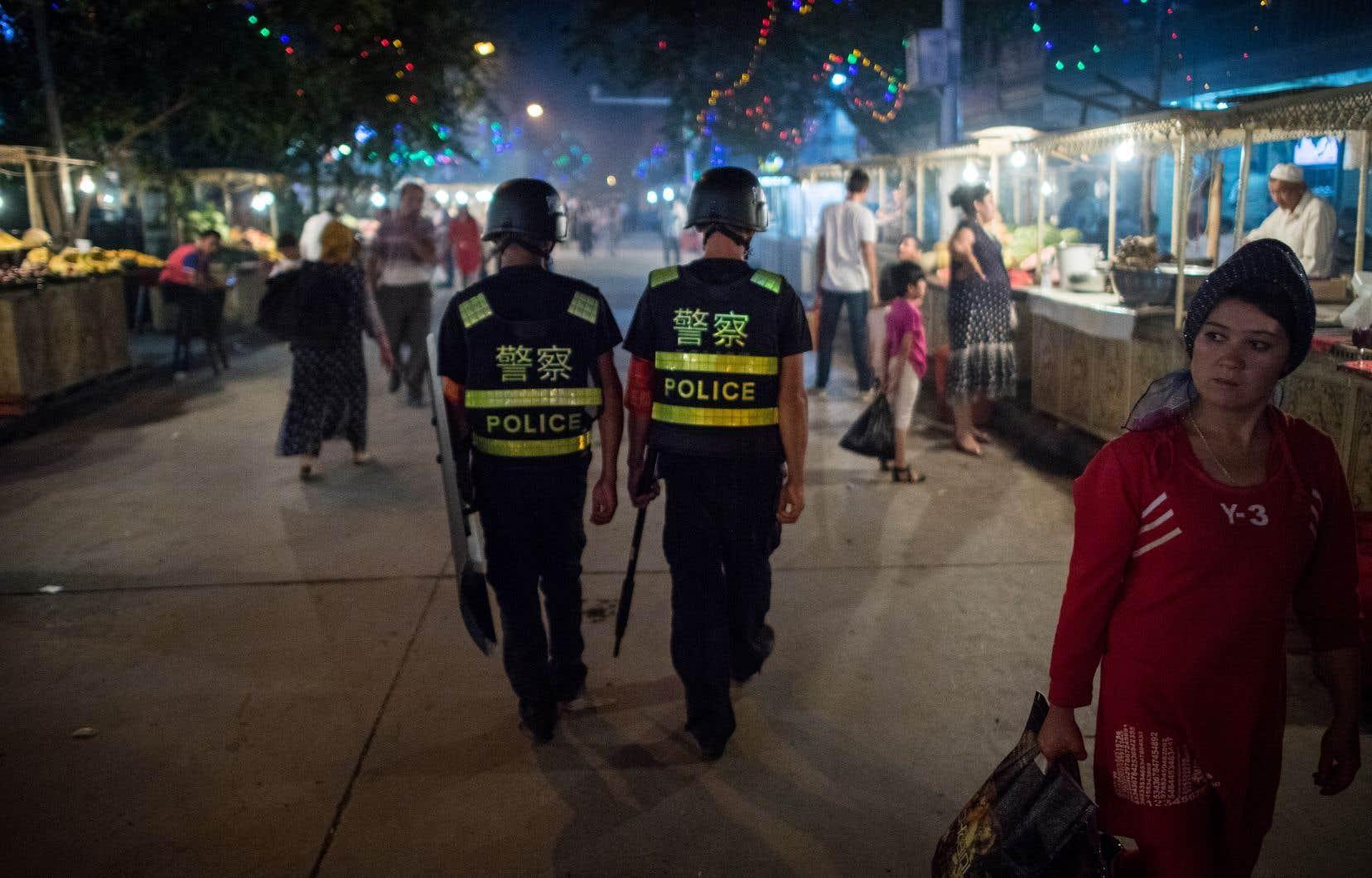 Des policierspatrouillent dans un marché de nuit près de la mosquée Id Kah à Kashgar, dans la région autonome ouïgoure du Xinjiang, en Chine.