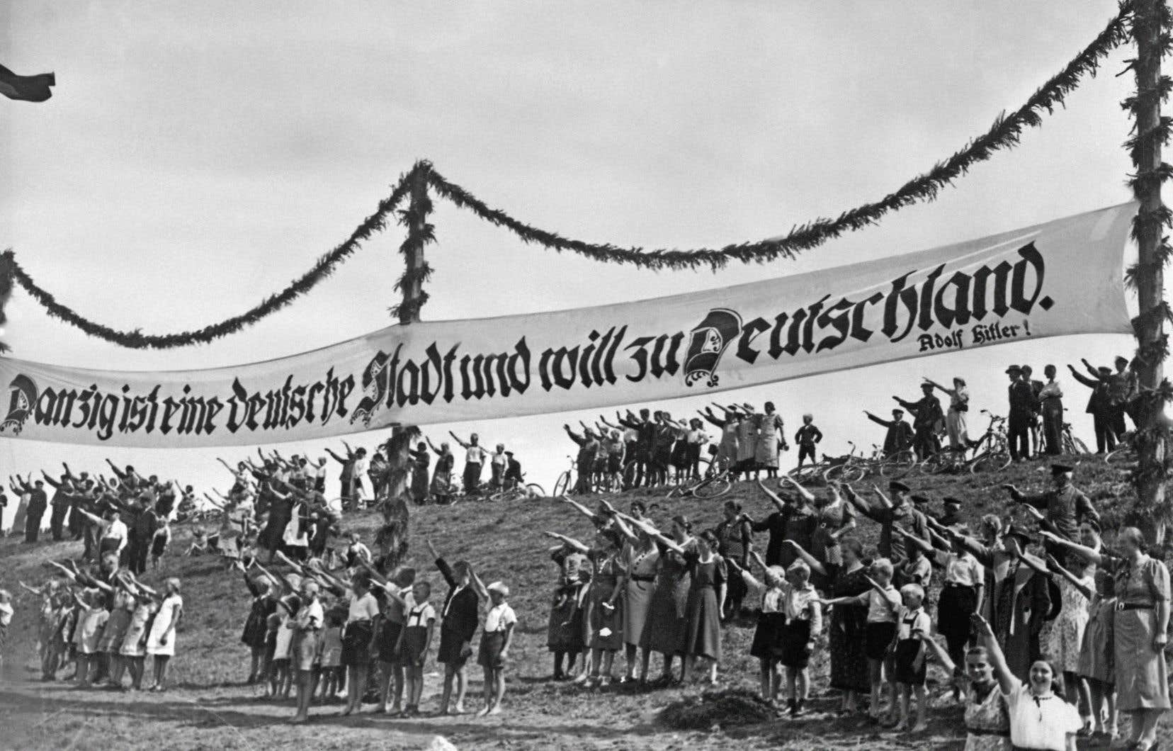 Des partisans nazis font le salut fasciste, en 1939, sous une bannière écrite en lettres gothiques réclamant le retour de la ville polonaise de Dantzig au sein de l'Allemagne.