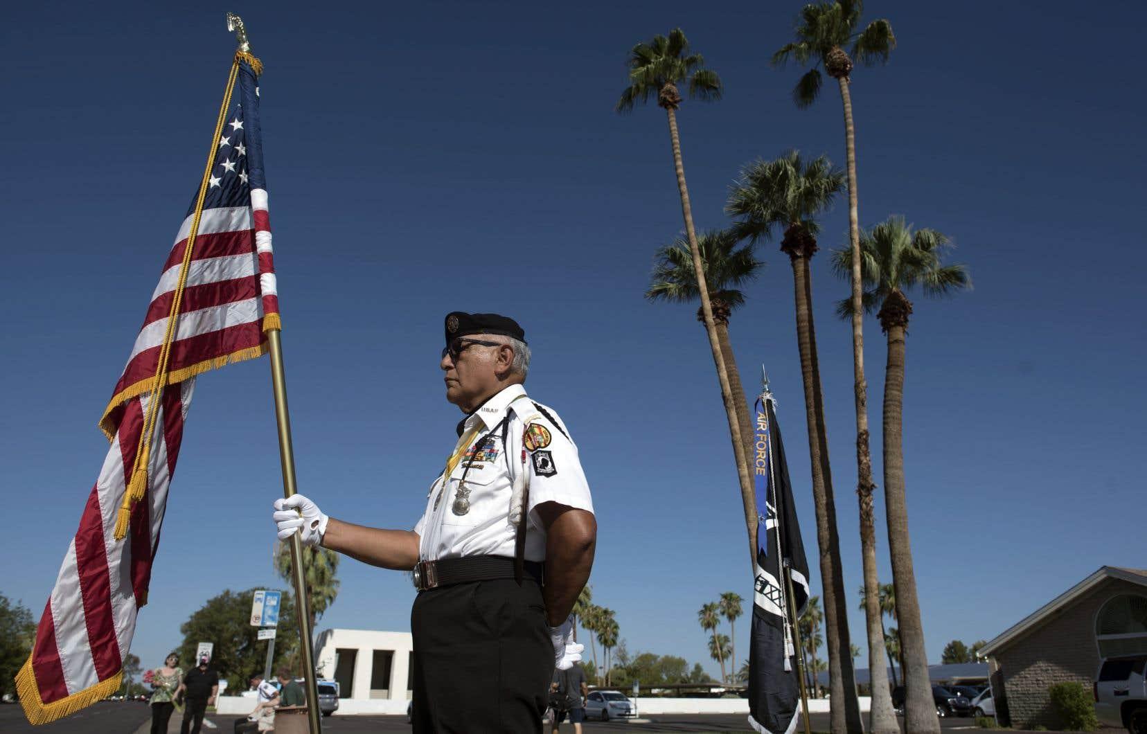 La garde d'honneur David Carrasco, 78 ans, porte le drapeau américain devant la morgue A.L. Moore-Grimshaw à Phoenix, en Arizona, où la dépuille du défunt sénateur John McCain est actuellement détenue, le 26 août 2018.