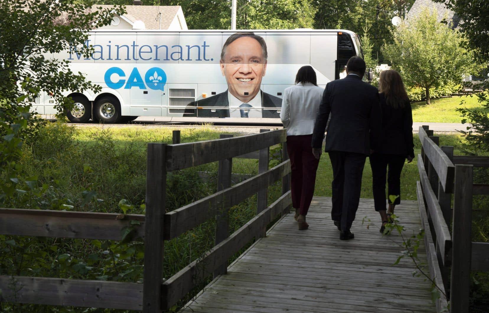 Le chef de la Coalition avenir Québec, François Legault, et les candidats locaux, Isabelle Charest, à gauche, et Geneviève Hébert se dirigeant vers l'autobus de campagne lors d'un arrêt de campagne à Bromont, au Québec, le lundi 27 août 2018