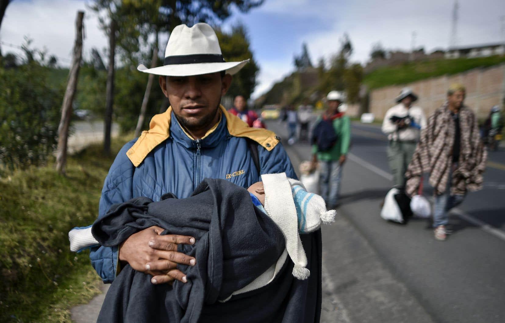 Comme des millions de Vénézuéliens, Richard Lomelly, 30ans, fuit la crise économique de son pays, Il marche avec son bébé, Tiago, dans ses bras le long de la route panaméricaine en Colombie pour se rendre au Pérou.