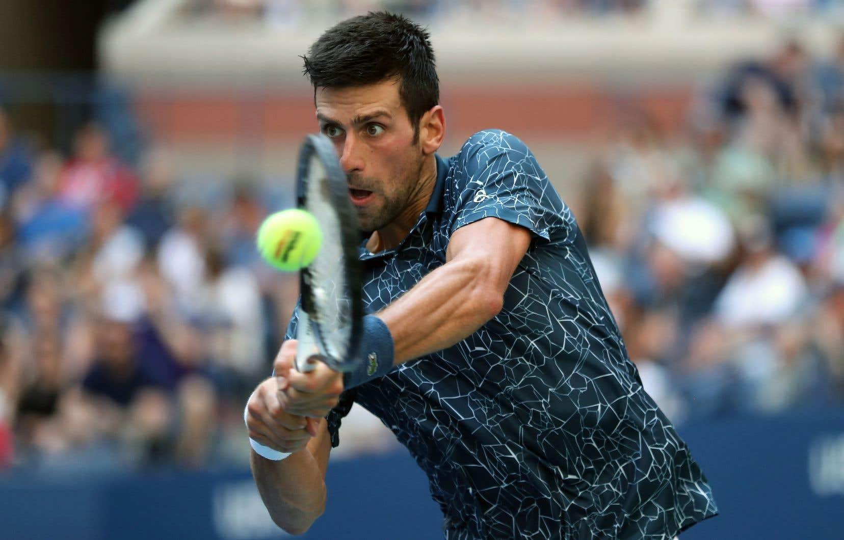 Novak Djokovic, qui a été incommodé par la chaleur, renvoie la balle au Portugais Joao Sousa.