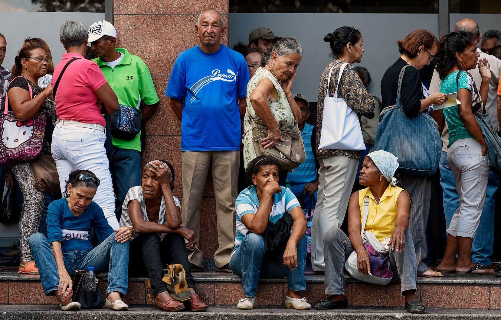 Des gens faisaient la file à l'extérieur d'une banque, lundi, à Caracas, pour mettre la main sur une partie de leur pension. Le pays est englué dans une grave crise économique depuis plusieurs mois.