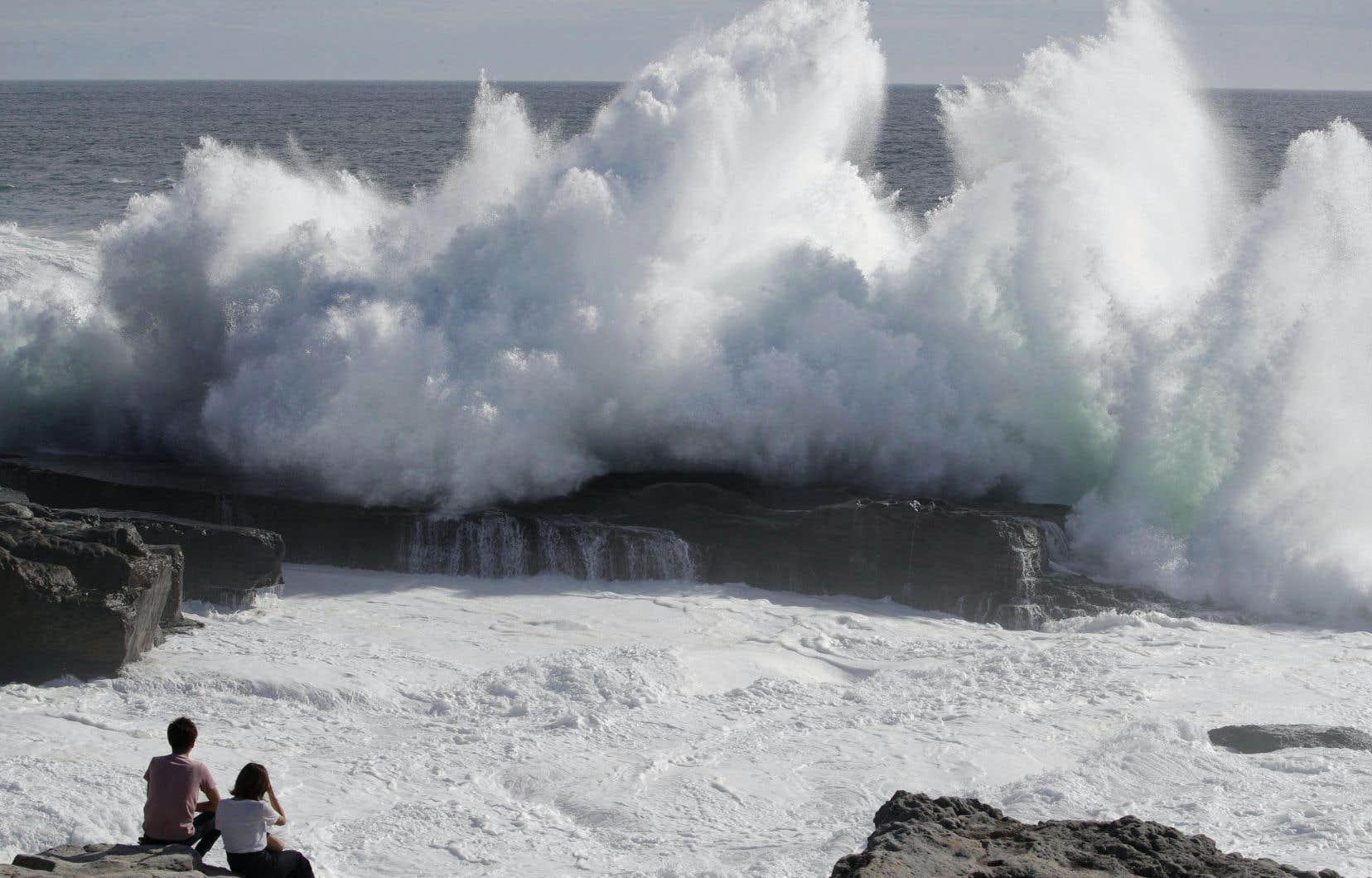 Deux personnes observent les vagues impressionnante qui frappent la côte de la ville de Shirahara, lundi.