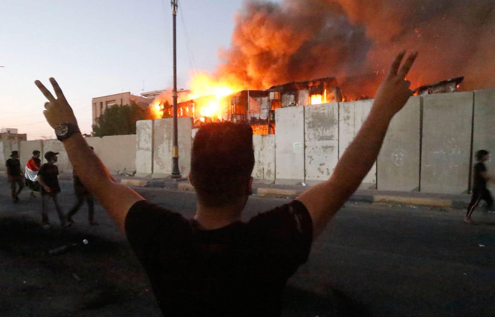 Des manifestants regardant un bâtiment public incendié, jeudi